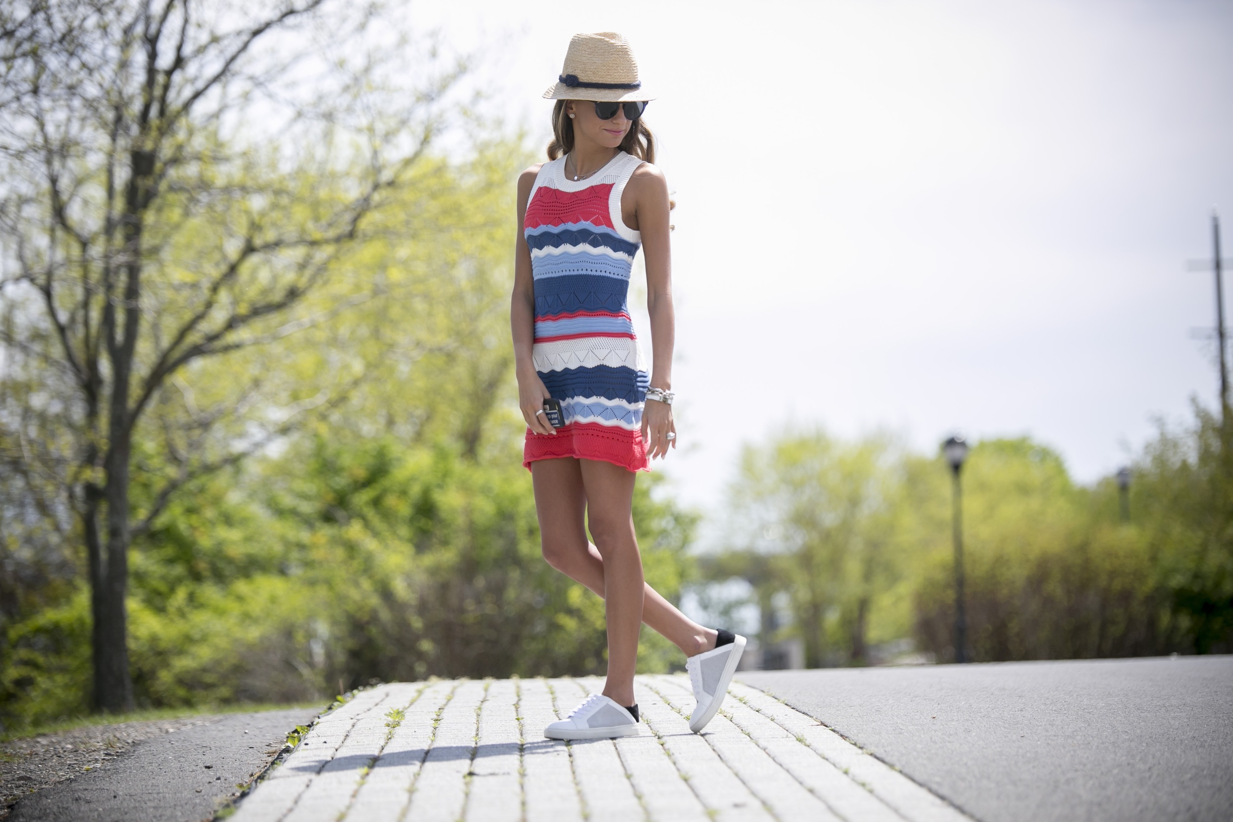 Knit mini dress worn with white sneakers and a straw hat