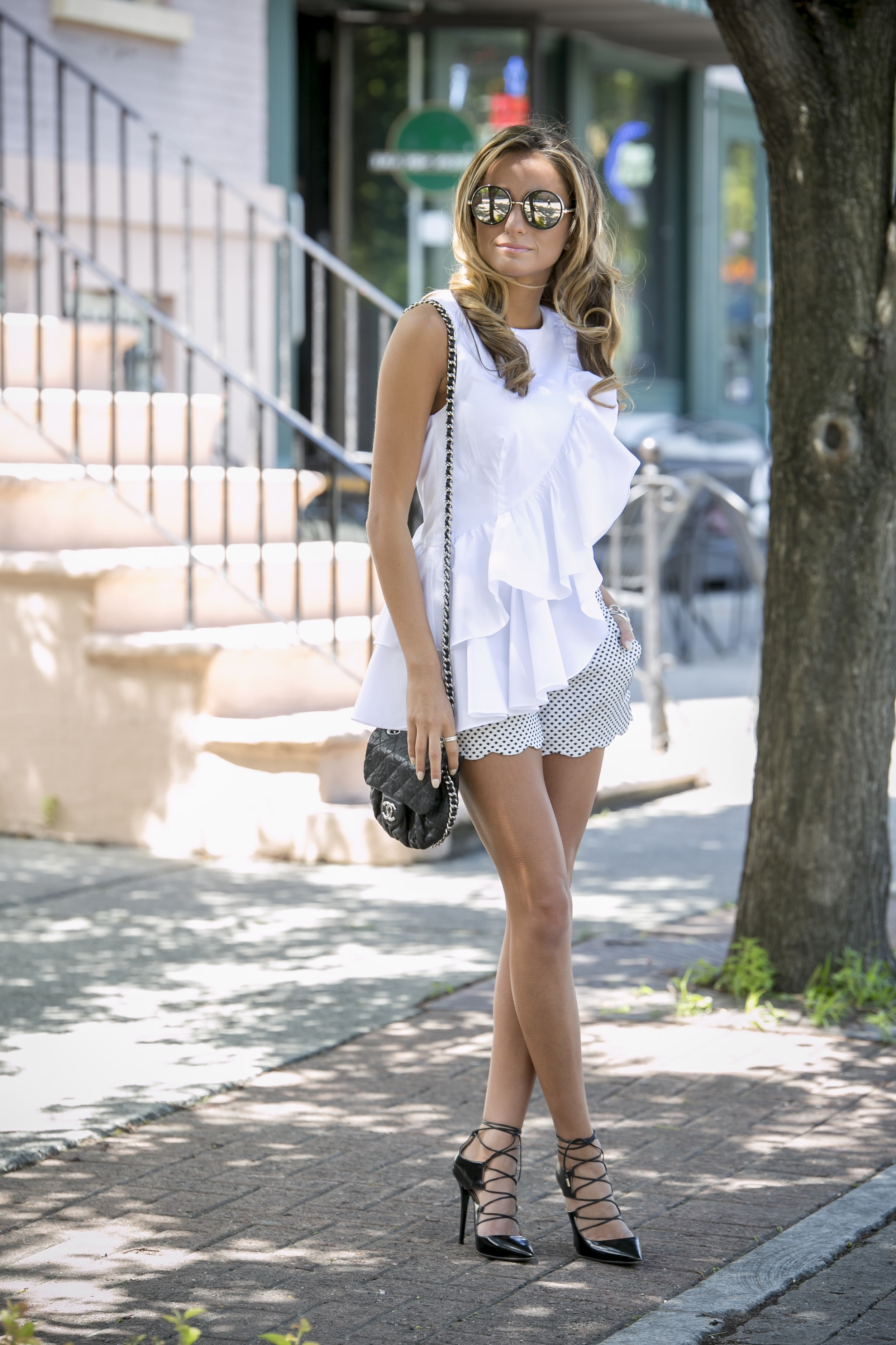 fashion blogger streetstyle in a ruffled intermix blouse, club monaco shorts, and jimmy chop lace up pumps and sunnies