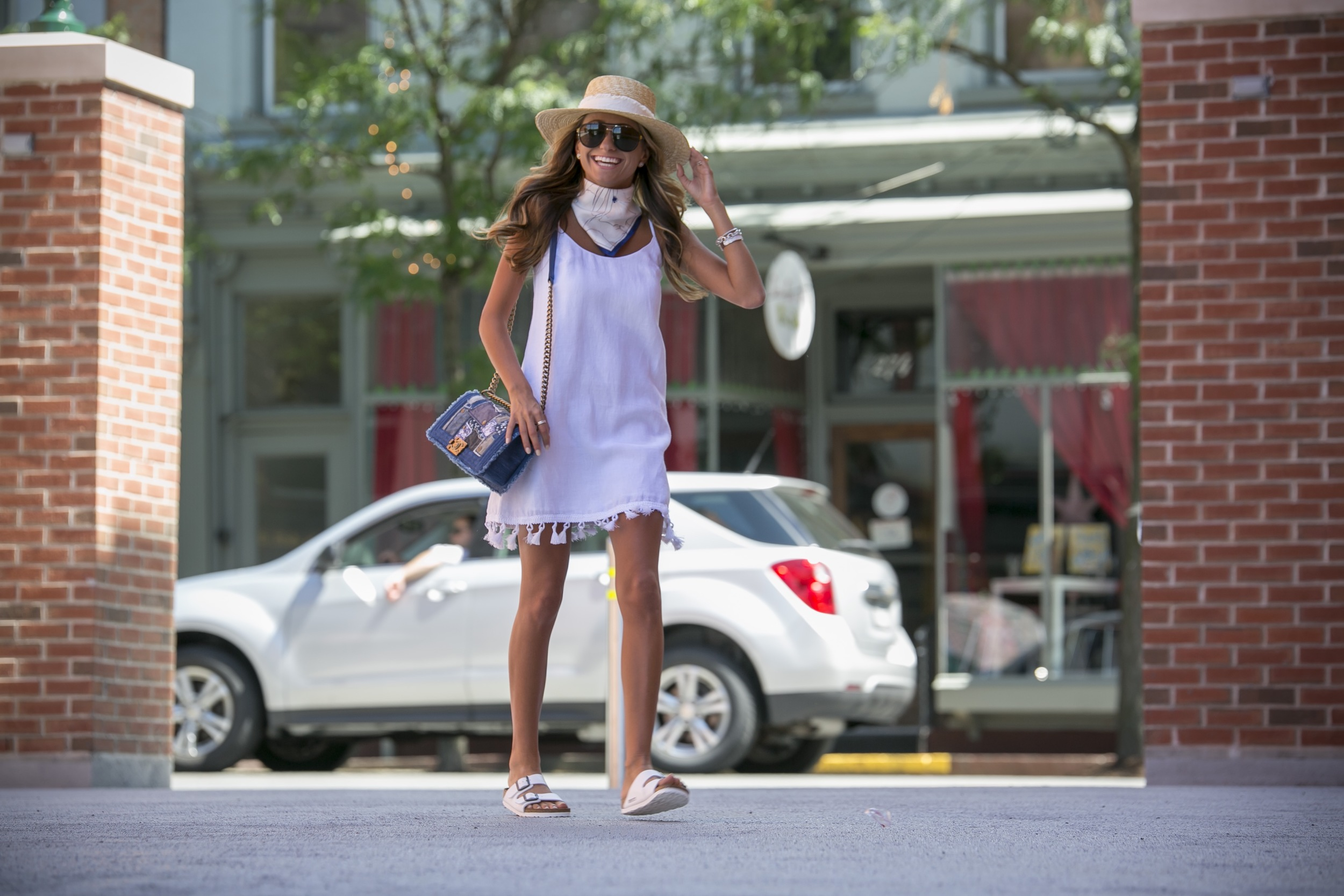 summer streetstyle with a little white dress detailed with tassels, a silk neck scarf, and white birkenstock sandals