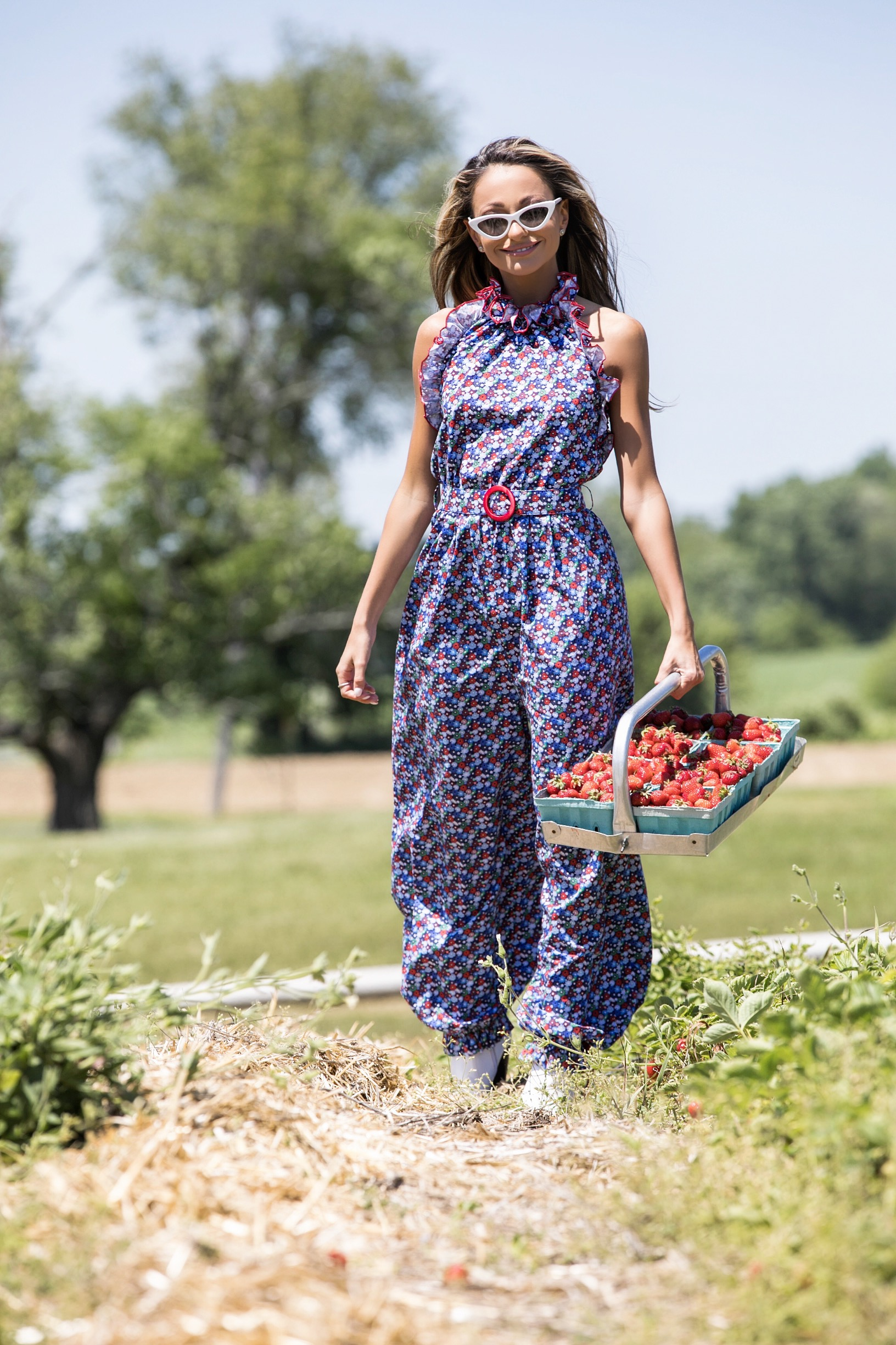 Lauren Recchia seen in a Gul Hurgel floral and halter jumpsuit while picking strawberries