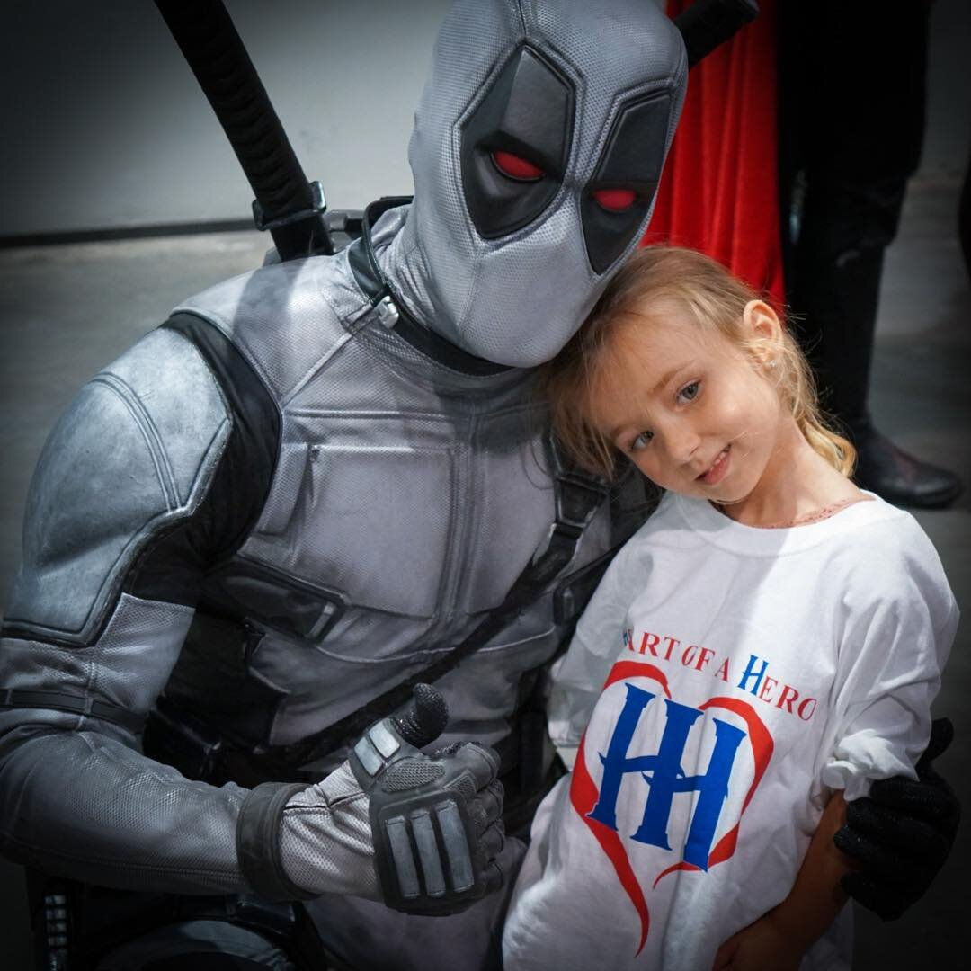 """Deadpool Cameo - Deadpool Cameo is the newest member to Heart Of a Hero, but he isn't new to making visits to children all around the world who need inspiration, encouragement, and a reason to smile. More than a year ago, Deadpool Cameo contacted our founder Ricky Mena in a private message asking for a few pointers and advice in how he could dawn the suit and begin his own journey in making a difference in the lives of children everywhere. After that short conversation, Deadpool Cameo ran with it and created an incredible platform of his own to better bring awareness and happiness to children fighting serious illness in his own unique way. After a year of working alongside organizations like """"Comicare"""" and independently being present at more than 100 public events creating a massive amount of awareness for children he visits, we decided it would best benefit the children and strengthen the power we had to help them if we joined forces! An alliance was born! Deadpool Cameo shares the same vision of visiting children as we do in the way of approaching each and every visit from a therapeutic standpoint rather than an entertainment based one. We are without a doubt excited to have Deadpool Cameo on our team and cant wait to tackle our mission statement of inspiring, motivating, and empowering children who need it most, TOGETHER! For more on Deadpool Cameo and to follow his personal journey more closely, please visit www.DeadpoolCameo.com"""