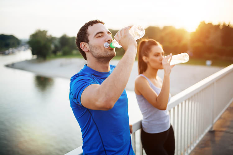 couple drinking water while standing on bridge.jpg