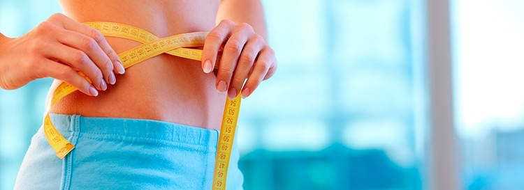 woman measuring her waist with a tape measure.jpg