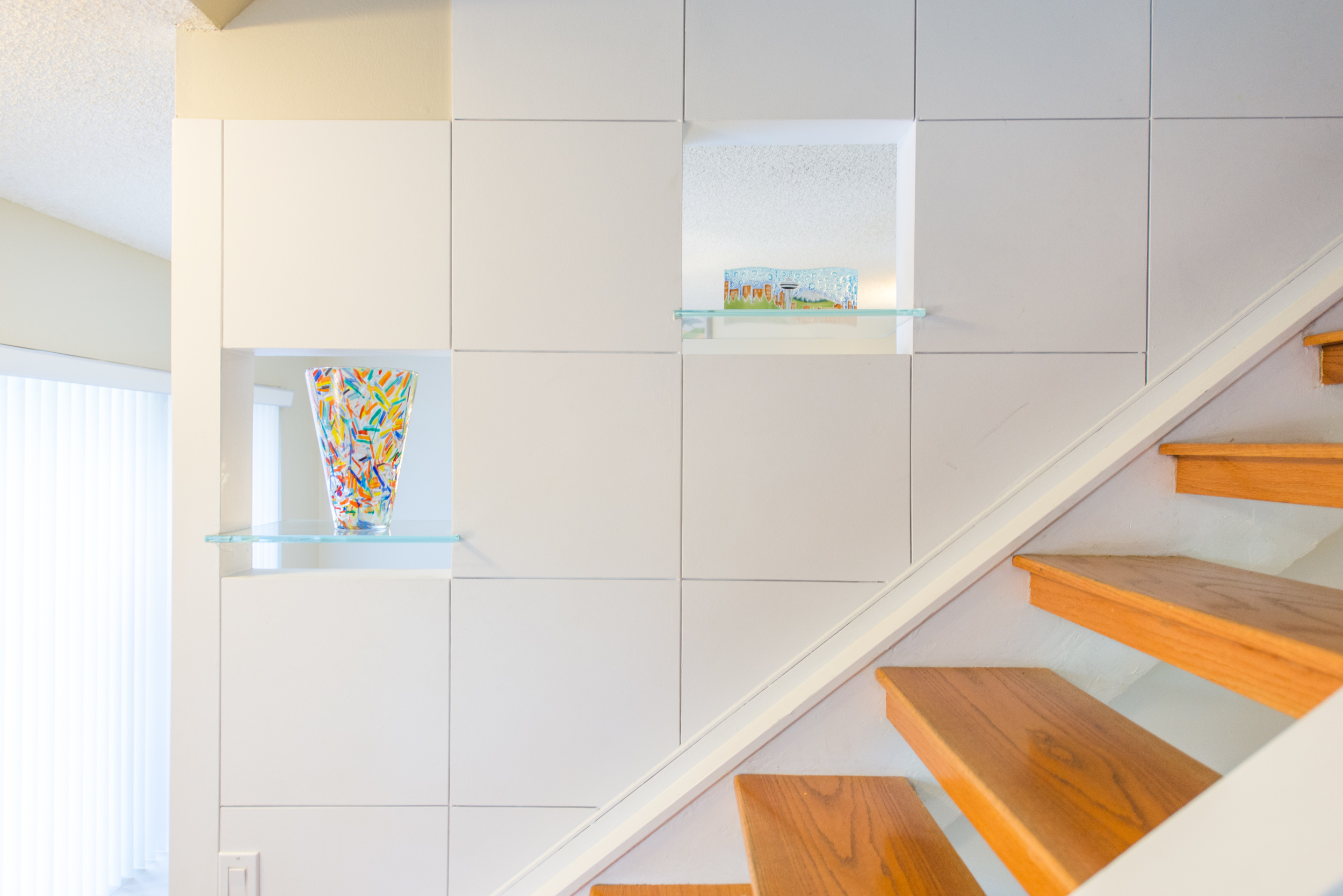 Beautiful detailing and floating glass shelves lead up the staircase to the 2nd floor.