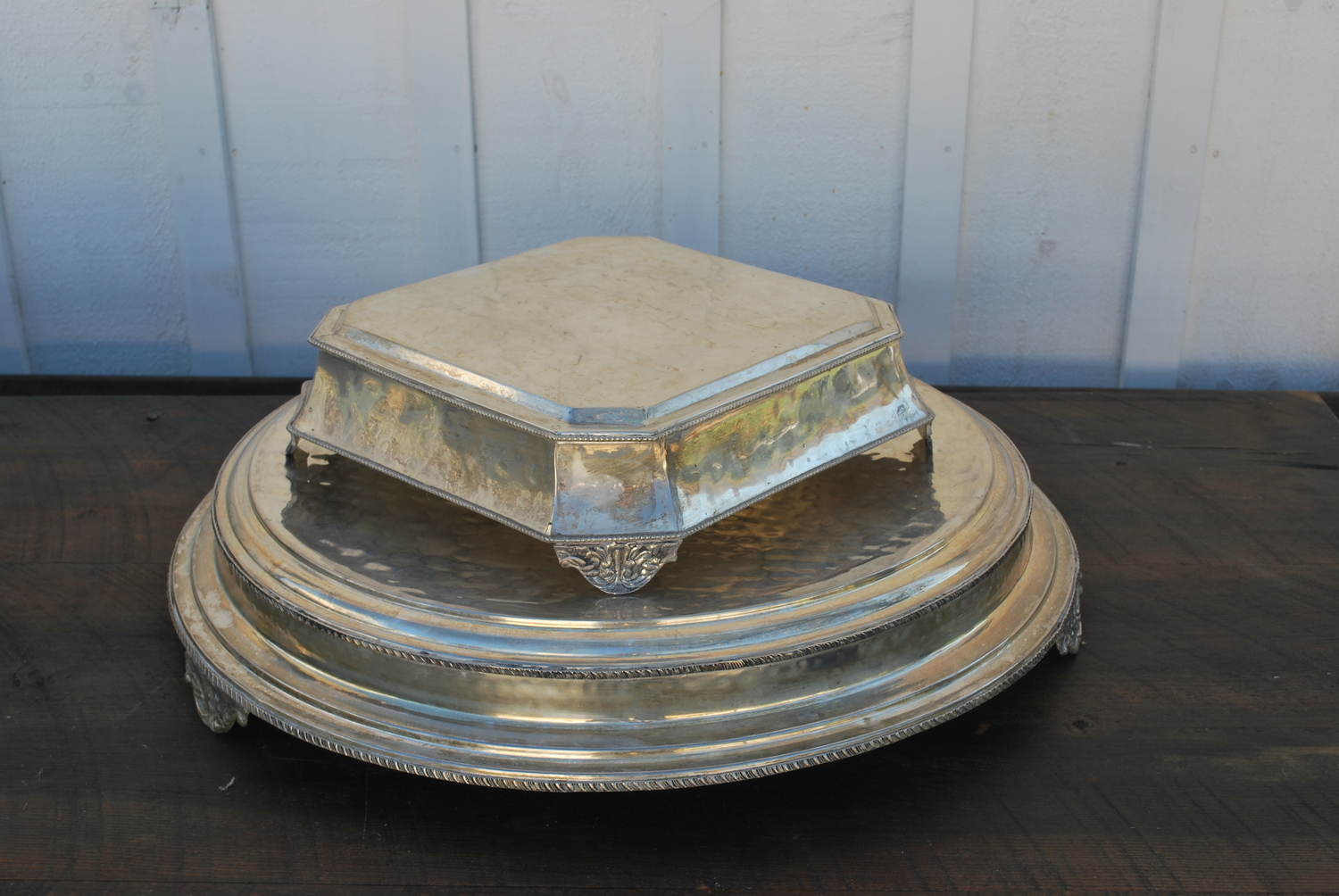 "Silver Cake Stands $15 each, 3 available. The largest is 22"" on the top and 27"" across bottom. The other is 12"" across the top and 15 1/2"" across the bottom. One more available - see picture."
