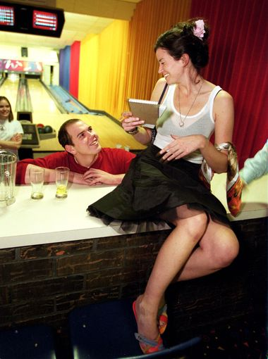 Olivia has the full attention of Joshua Grooms of the Landmark Bowling Alley in Peoria, Ill., where she sought residents' reactions to her 'Sex and the City' outfits in 2002.  (Photo: Anne Ryan, USA TODAY)