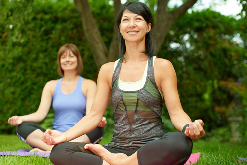 A woman doing yoga who is happy with her smile.