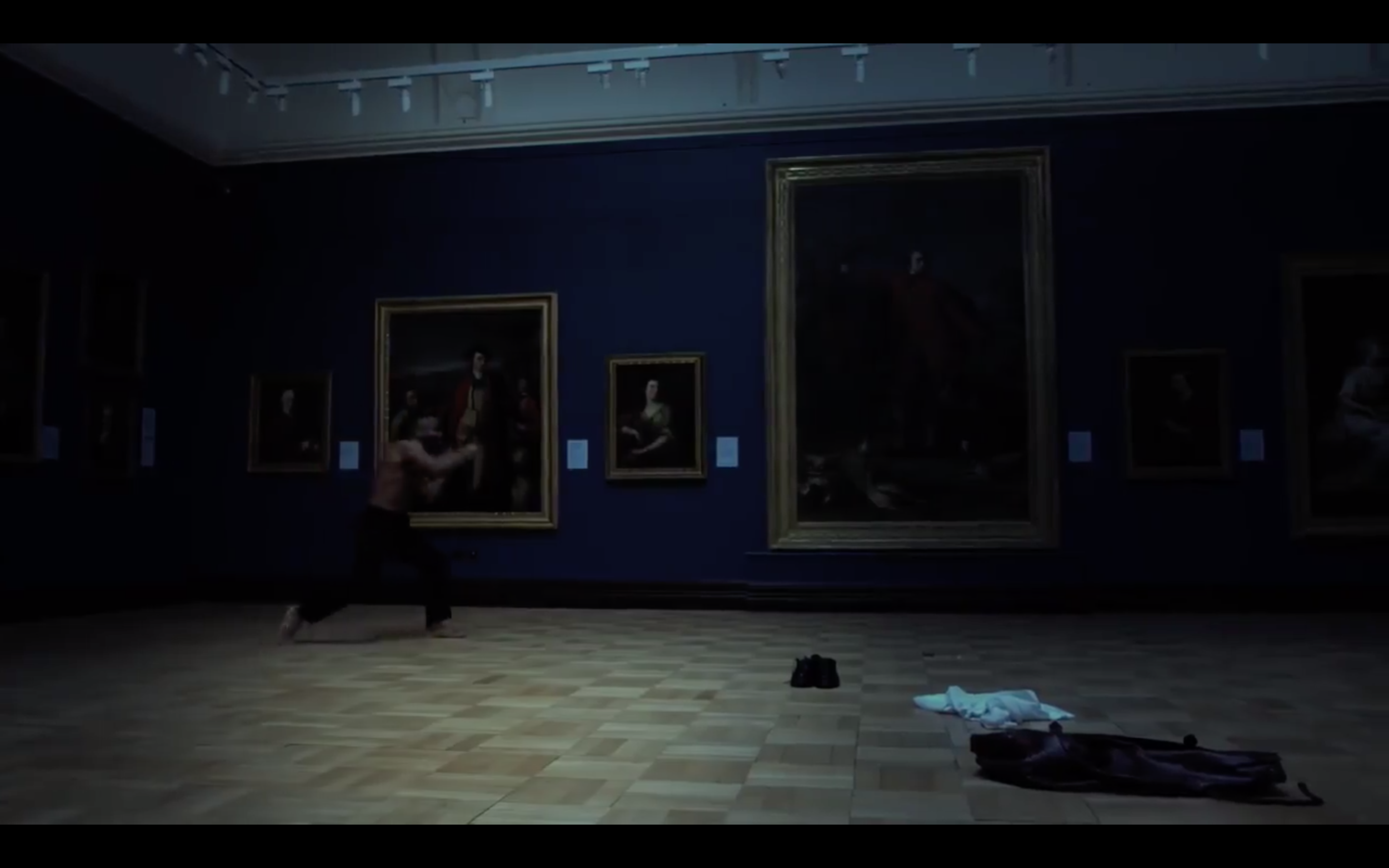"""He removes his shirt and begins to shadowbox with the paintings of Scottish national figures."""