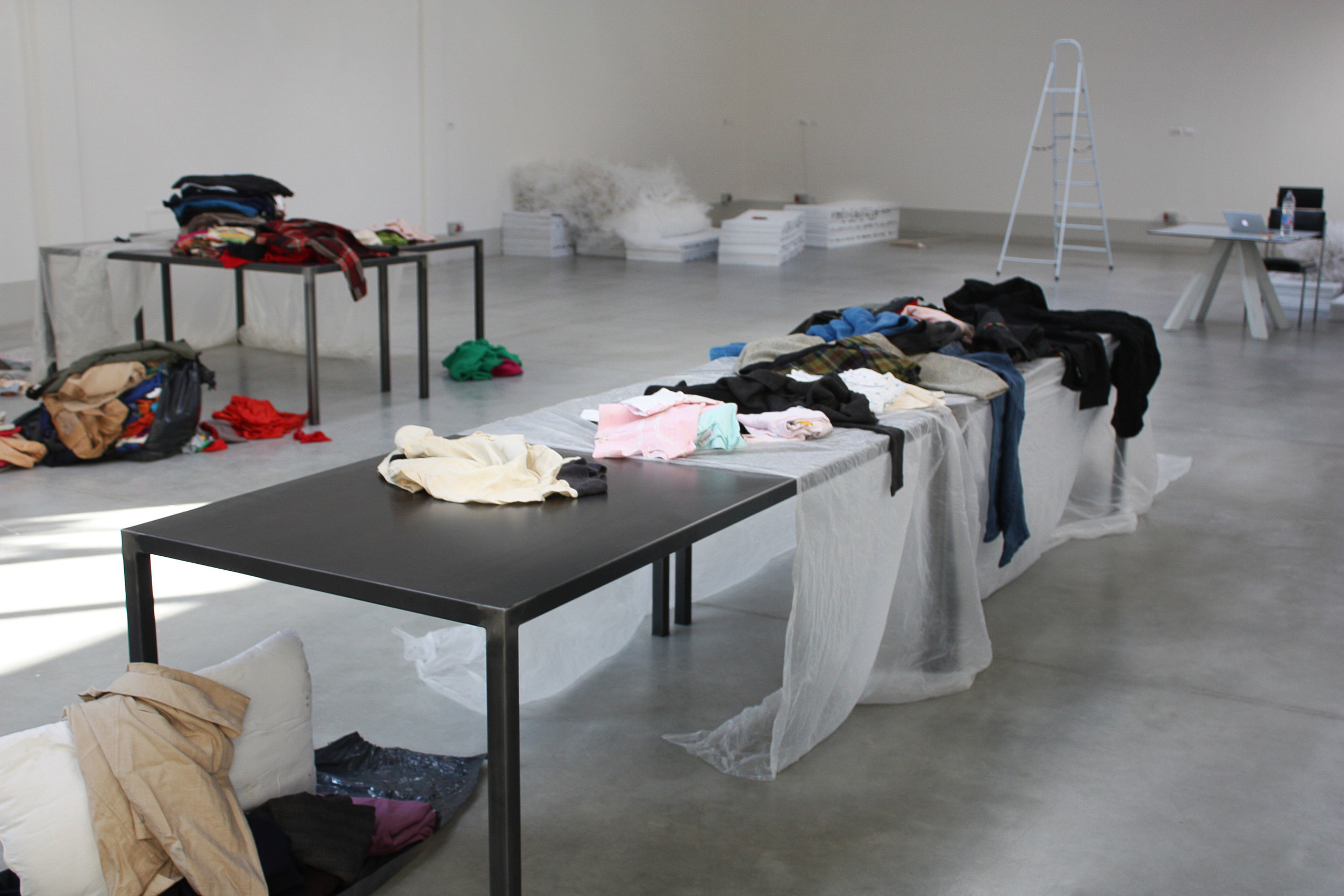 Luca Vanello's garments spread out in the workspace
