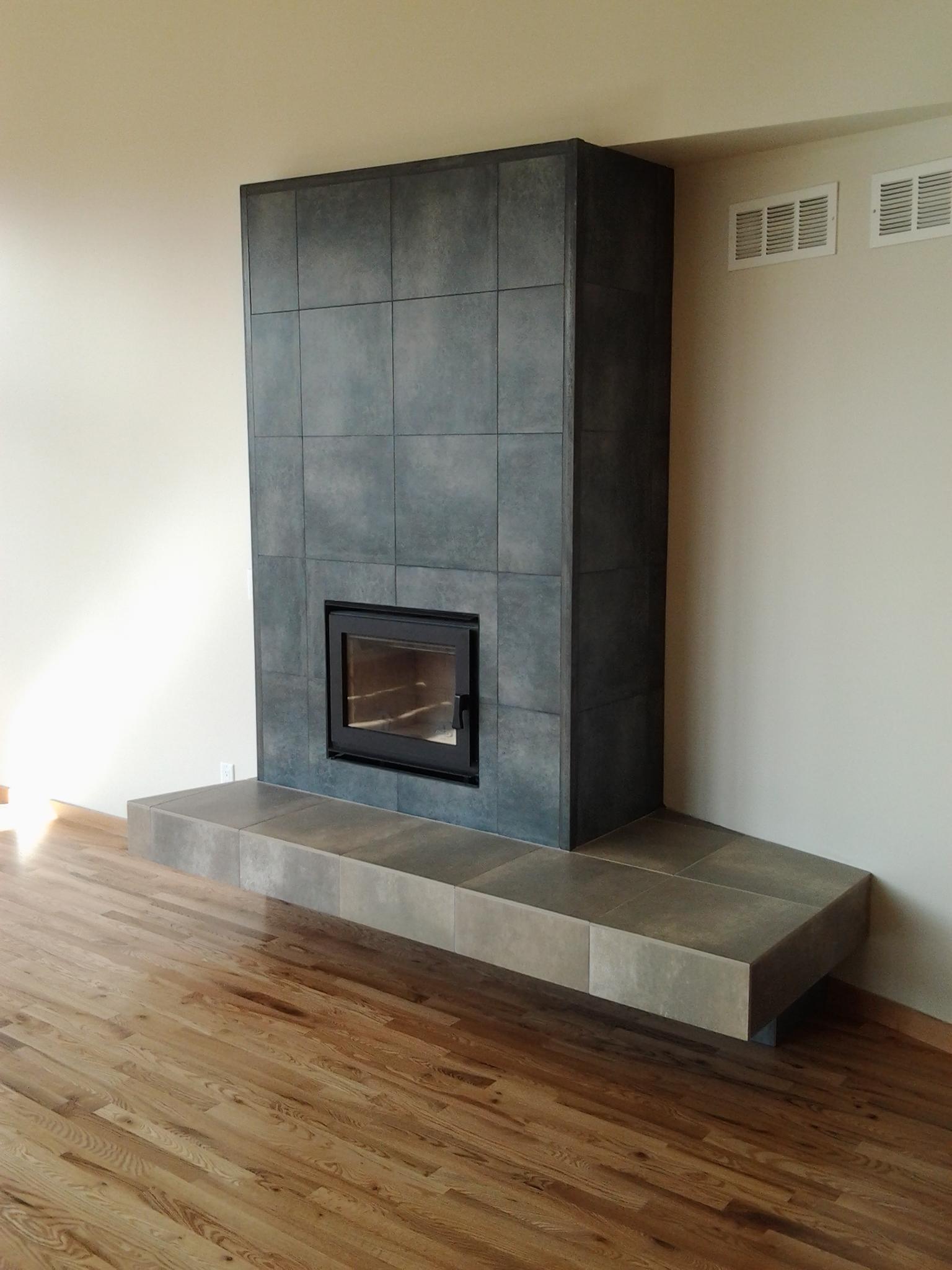 Metal framed porcelain fireplace with 'floating' bench.