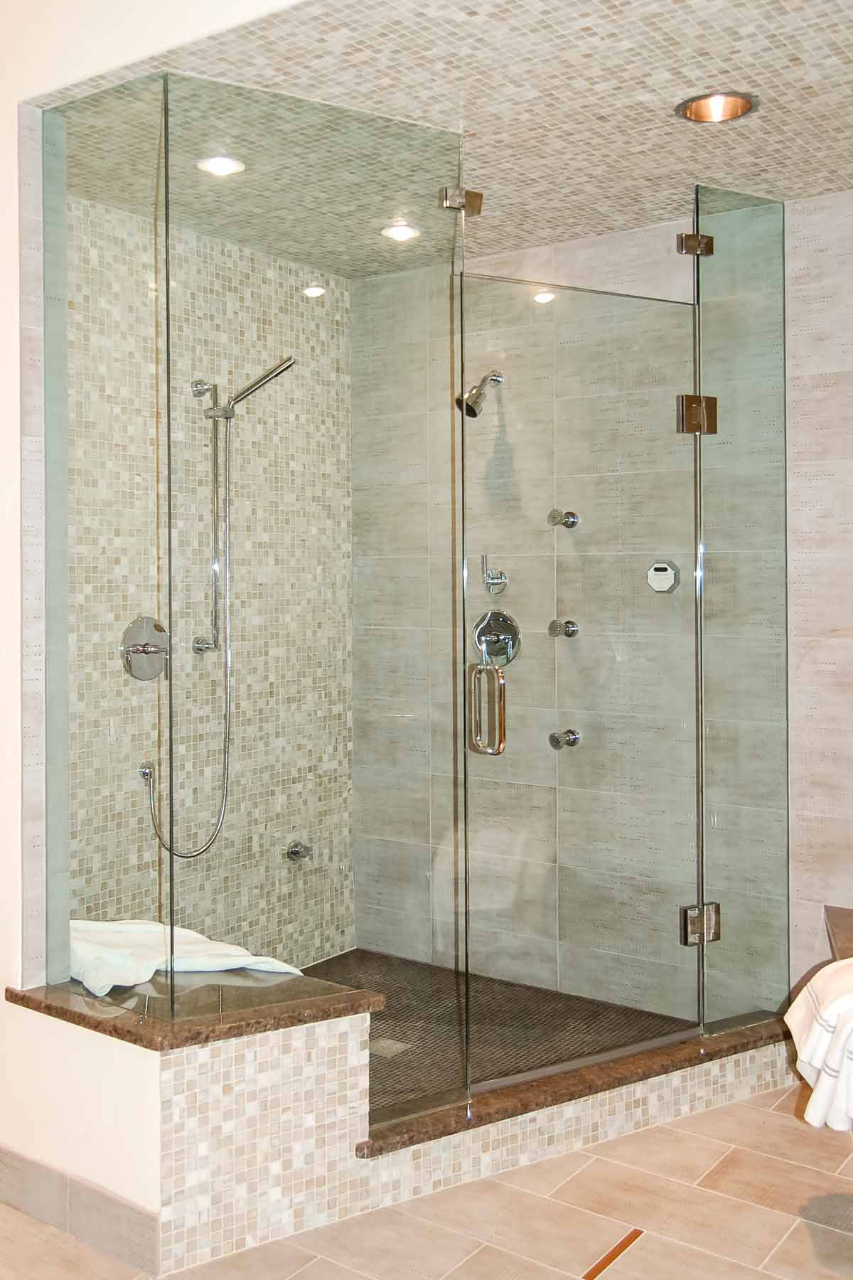 The master suite has a side by side steam shower and tub that combines glass and porcelain tiles.