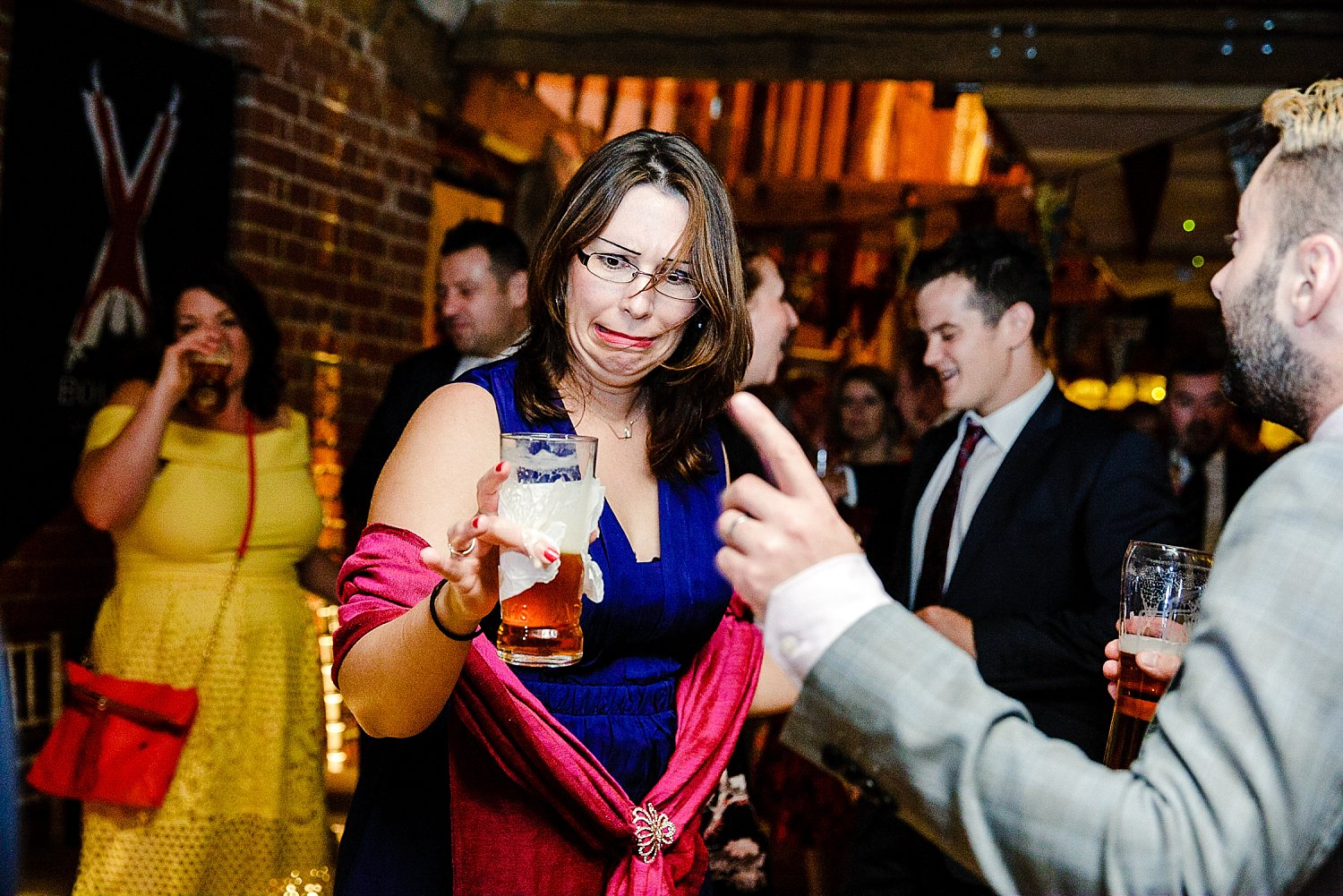 Tudor Barn Wedding Guest Spilling her beer on the dancefloor