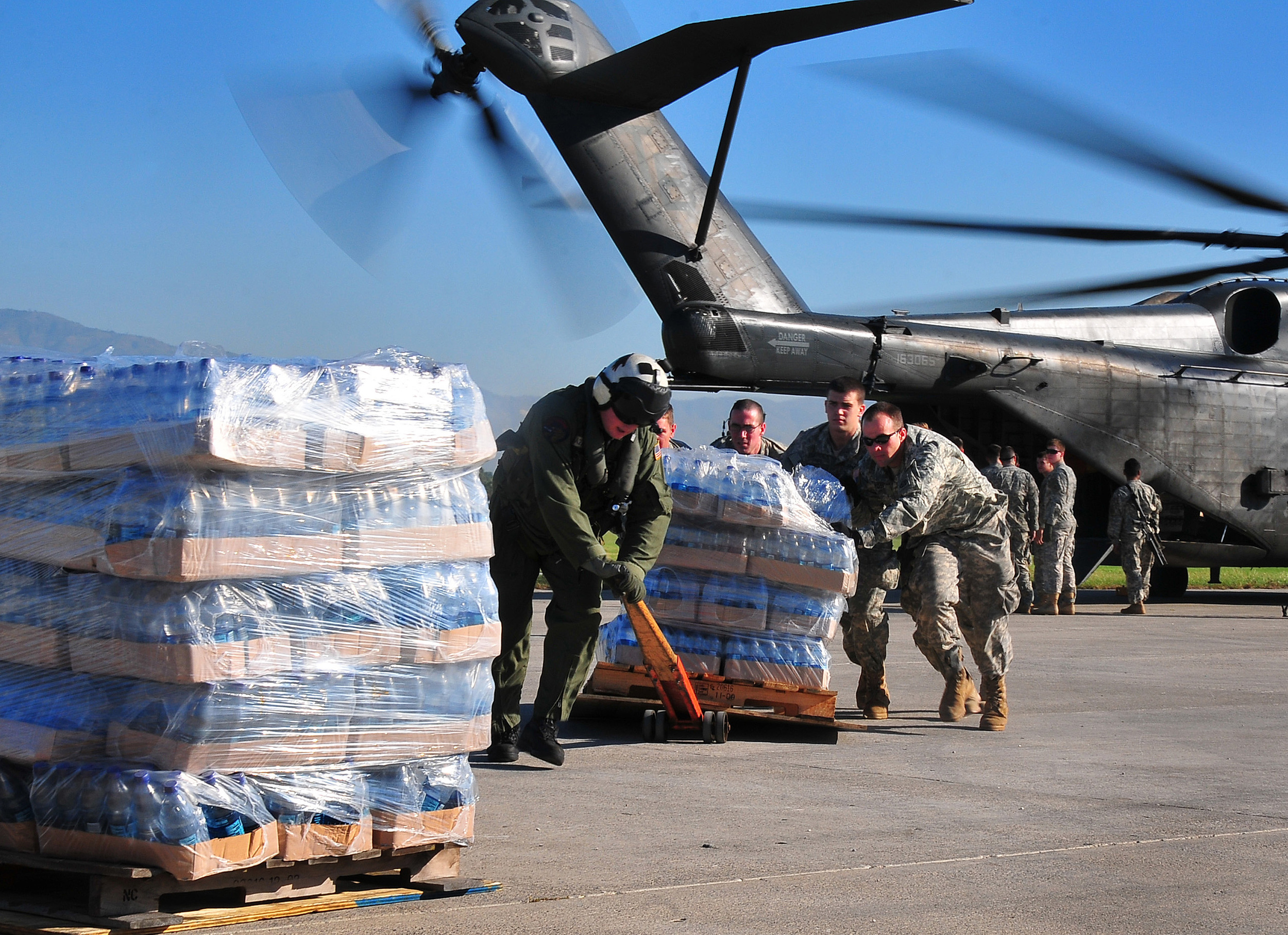 U.S. Army soldiers help the crew of a U.S. Navy MH-53E Sea Dragon helicopter from the aircraft carrier USS Carl Vinson (CVN 70) unload food and supplies at the airport in Port-au-Prince, Haiti.  Daniel Barker, US Navy.