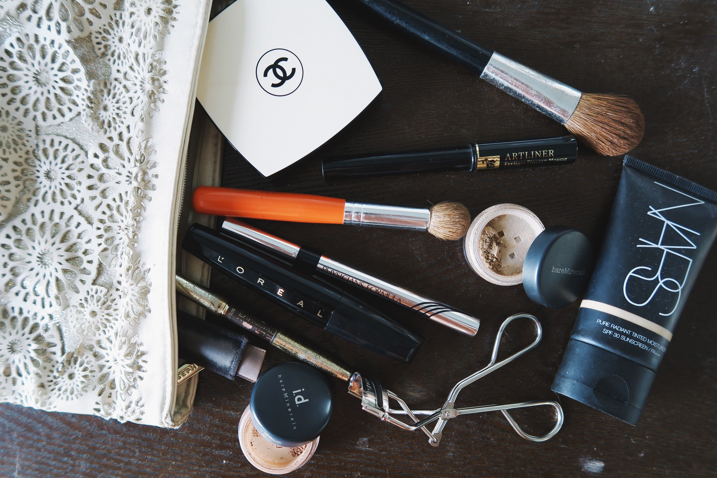 The contents of Maureen's Makeup Bag: Chanel Les Beiges N40, Lancome Artliner, Bare Minerals Shadow in Summer Physician's Formula Eye Liner, L'Oreal Voluminous Mascara, Lancome Le Crayon Poudre in Brunet,Bare Minerals Summer I.D. in Cashmere, Shu Uemura Eyelash curlers, Nars Pure Radiand Tinted Moisturizer in Shade #2.