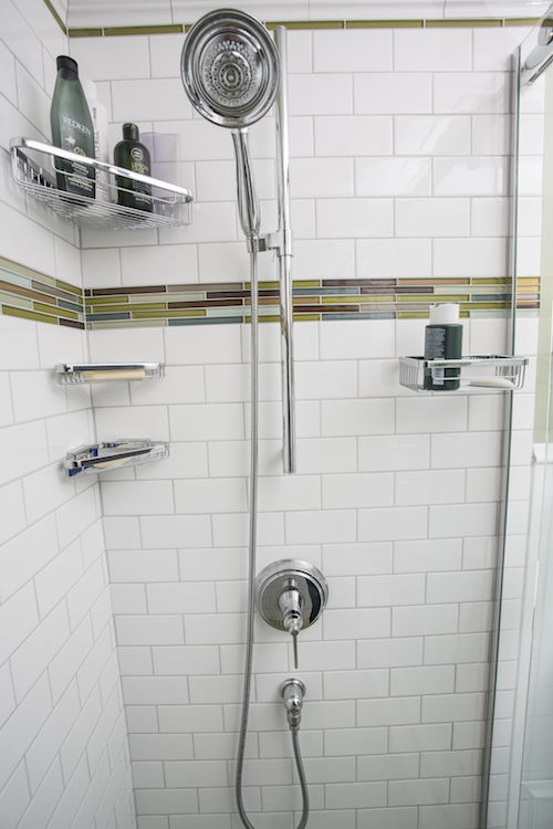 Shower with white subway tile and green mosaic tile
