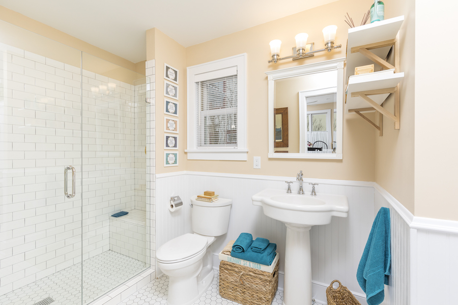 Bathroom with tan walls, pedestal sink, and standing shower