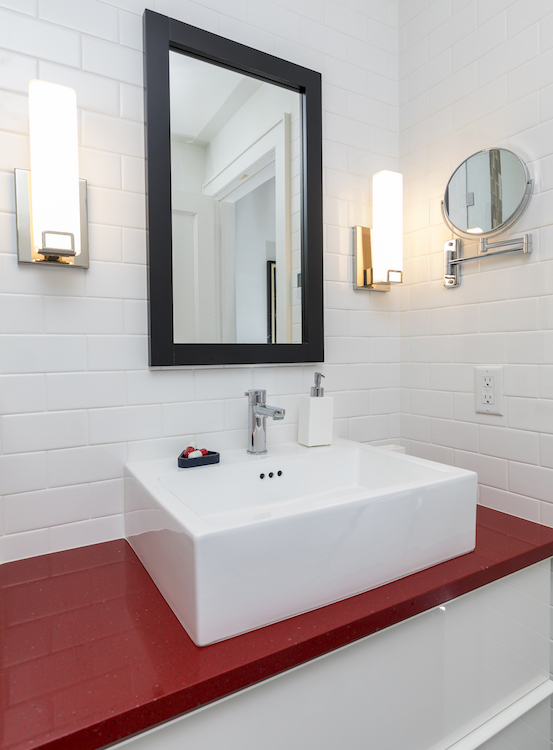 White bathroom sink with red counter