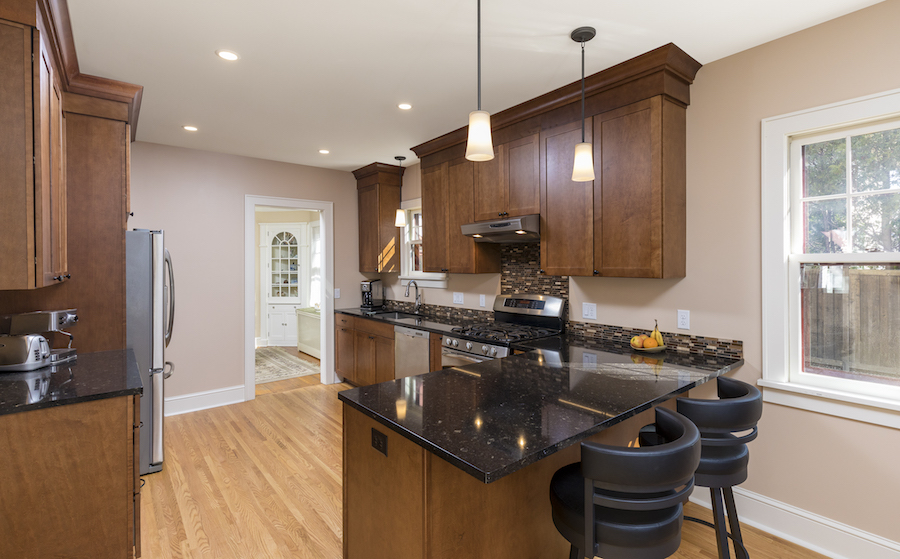 Kitchen with walnut cabinets and black granite counters