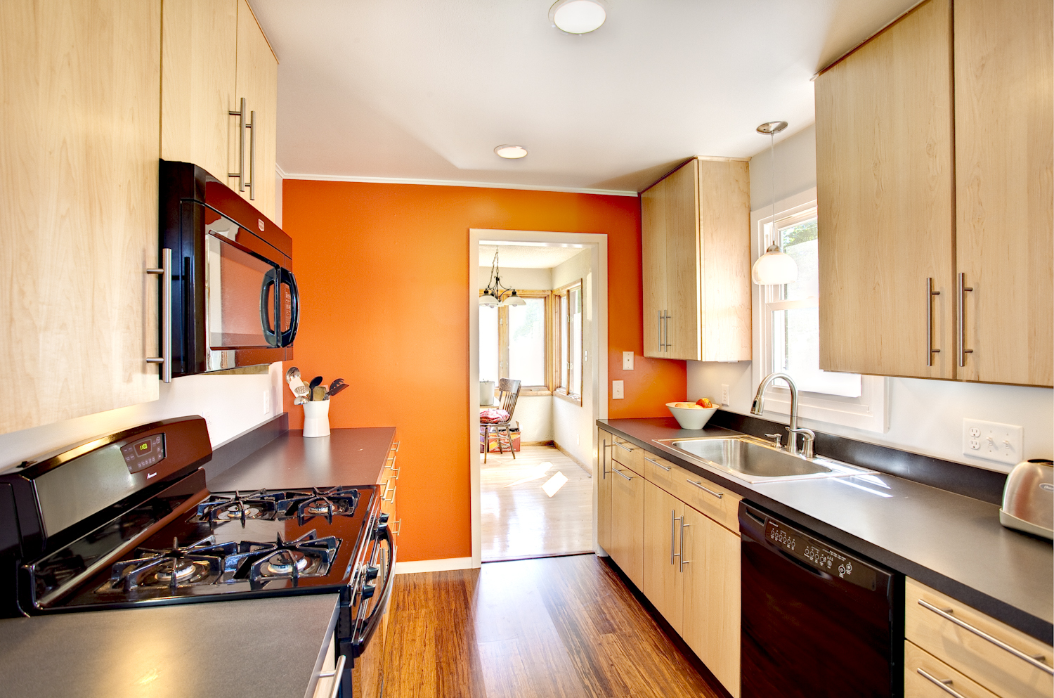 Kitchen with orange walls and light wood cabinets