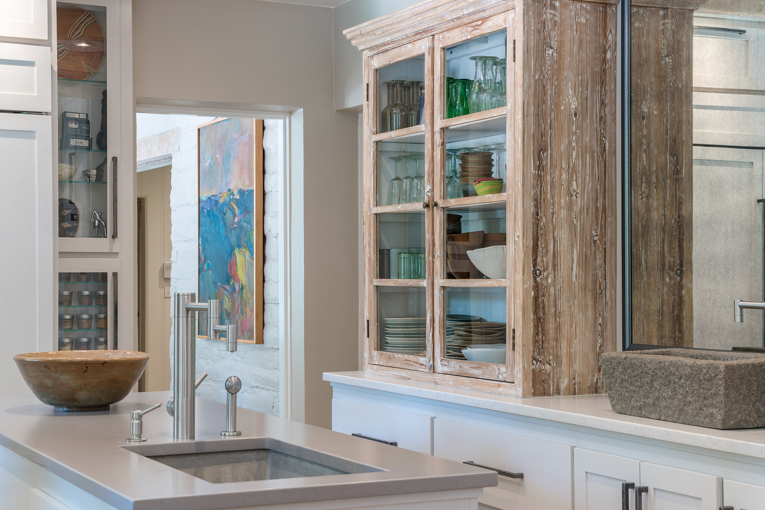 The kitchen is simple and restrained. I balanced elements once again by juxtaposing an old stone vessel sink and a stripped-down old farmhouse cabinet with sleek modern surfaces and appliances. I framed a large, antiqued mirror in iron and placed it across from the windows to bring in reflected light and views of their beautiful backyard.