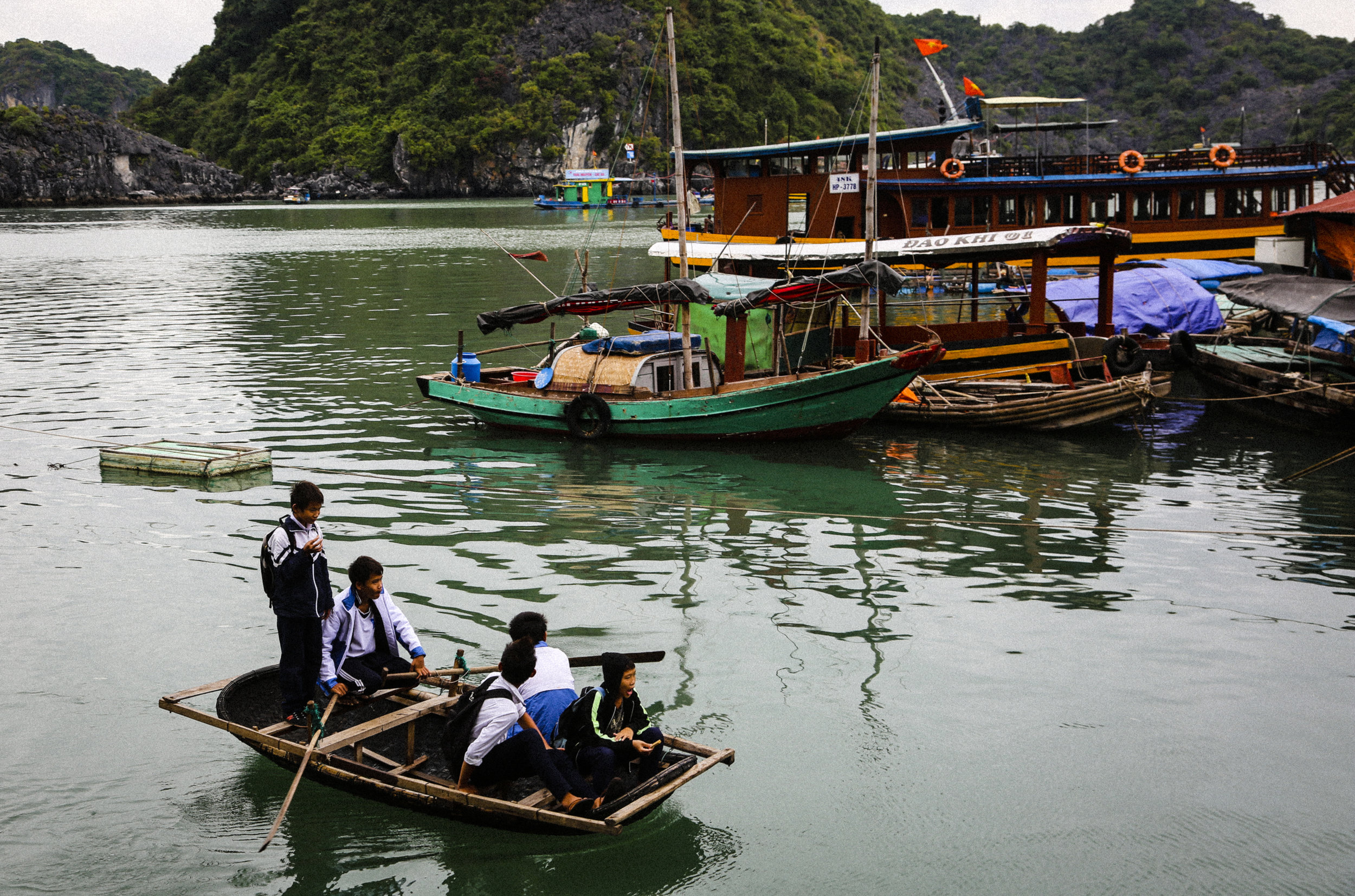 Children venture home from school on this hand made boat in Halong Bay.