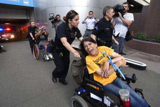 ADAPT protester  Lonnie Smith arrested at a sit-in at Denver US Senator Cory Gardner's office opposing GOP health care bill cuts to Medicaid (Jon Leyba/The Denver Post via AP)