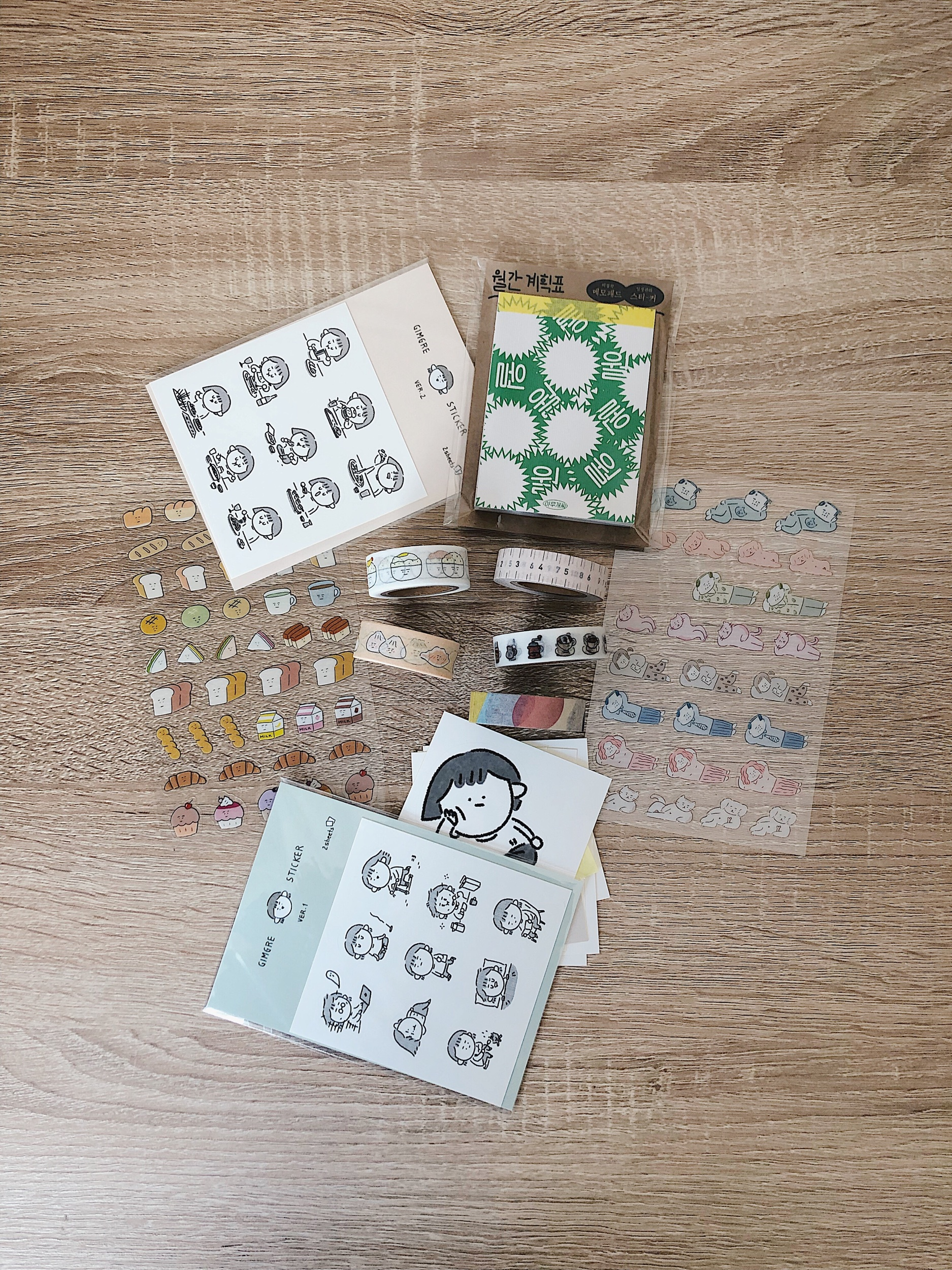 "Top center: green monthly memo pad by Ahmugae-c  Sticker sheets: hand-drawn stickers by Gimgre, bread stickers by Bakban Design, ""family lying down"" stickers by Ajassi  Masking tapes: rice and dumpling by Bakban Design, coffee by 3months, pink ruler and patterns by oh, lolly day!"