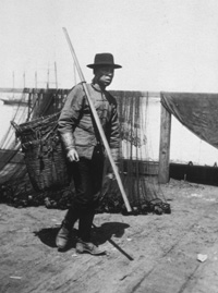 Chinese fish peddler on Santa Cruz Railroad wharf, c.1880s. The baskets in this photograph are empty and nested together. When full, the two baskets were suspended from the ends of the carrying pole that he is carrying over his shoulder. Photo Credit: UCSC Special Collections.