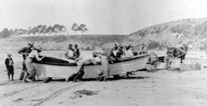 Fishermen pulling boat on rollers up China Beach,1913. This remarkable photograph was taken looking west, with present-day Park Avenue in the distance on the left, and New Brighton State Beach on the right. The box used to ship the fish is on the beach just to the right of the horse. The fish were probably shipped by train from the local railroad stop nearby. Credit: Sutton Family Collection.