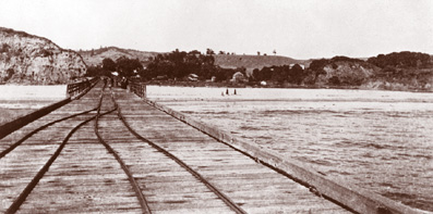 Aptos Wharf and Aptos, c. 1882. Taken during the Spreckels era looking north, this rare photograph shows the sandstone bluff that is part of today's Seacliff State Beach. The treeless hills in the distance are what we now call Aptos Village, while the buildings visible to the right of the wharf are part of Spreckels' hotel complex. The railroad tracks on the wharf were used to move cargo on small horse-drawn railcars. No railroad locomotives ever came out on the wharf. Photo Credit: Preston Sawyer Collection, University of California, Santa Cruz.