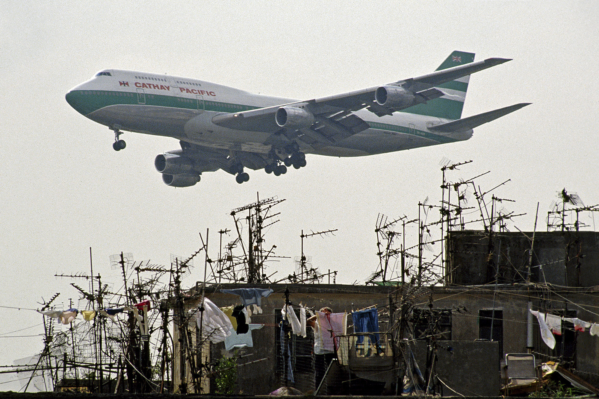 Cathay Pacific jet passing Walled City rooftops. 1989