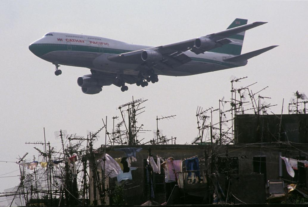 a Cathay Pacific jet passing Walled City rooftops. 1989.jpg