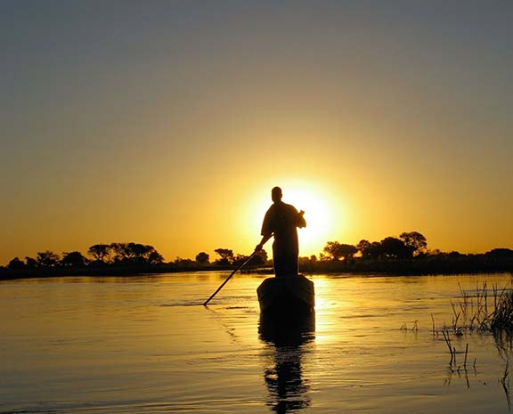 traversing high waters in a traditional dugout.Okavango Delta