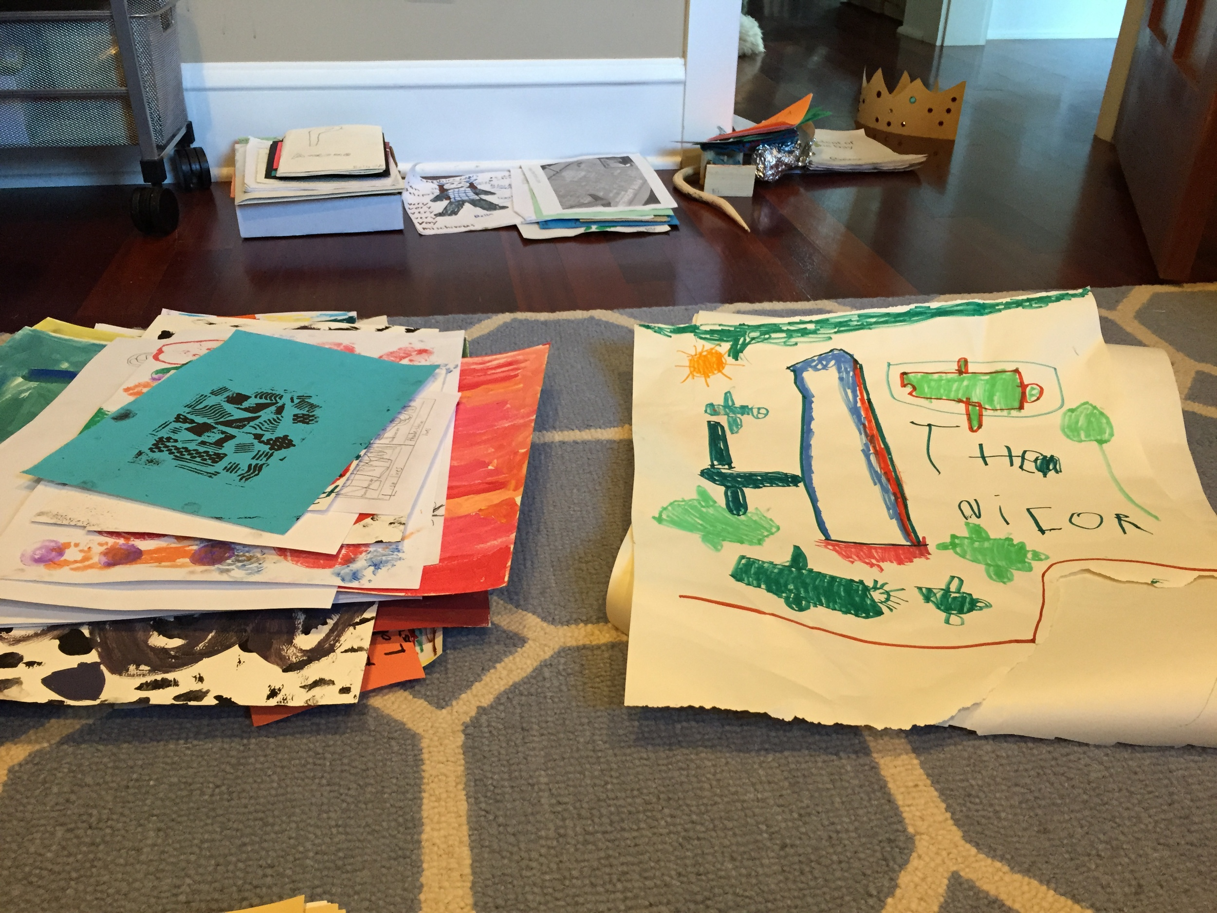 Two piles: one pile is artwork from my daughter and one from my son. These piles have artwork that will be given away.