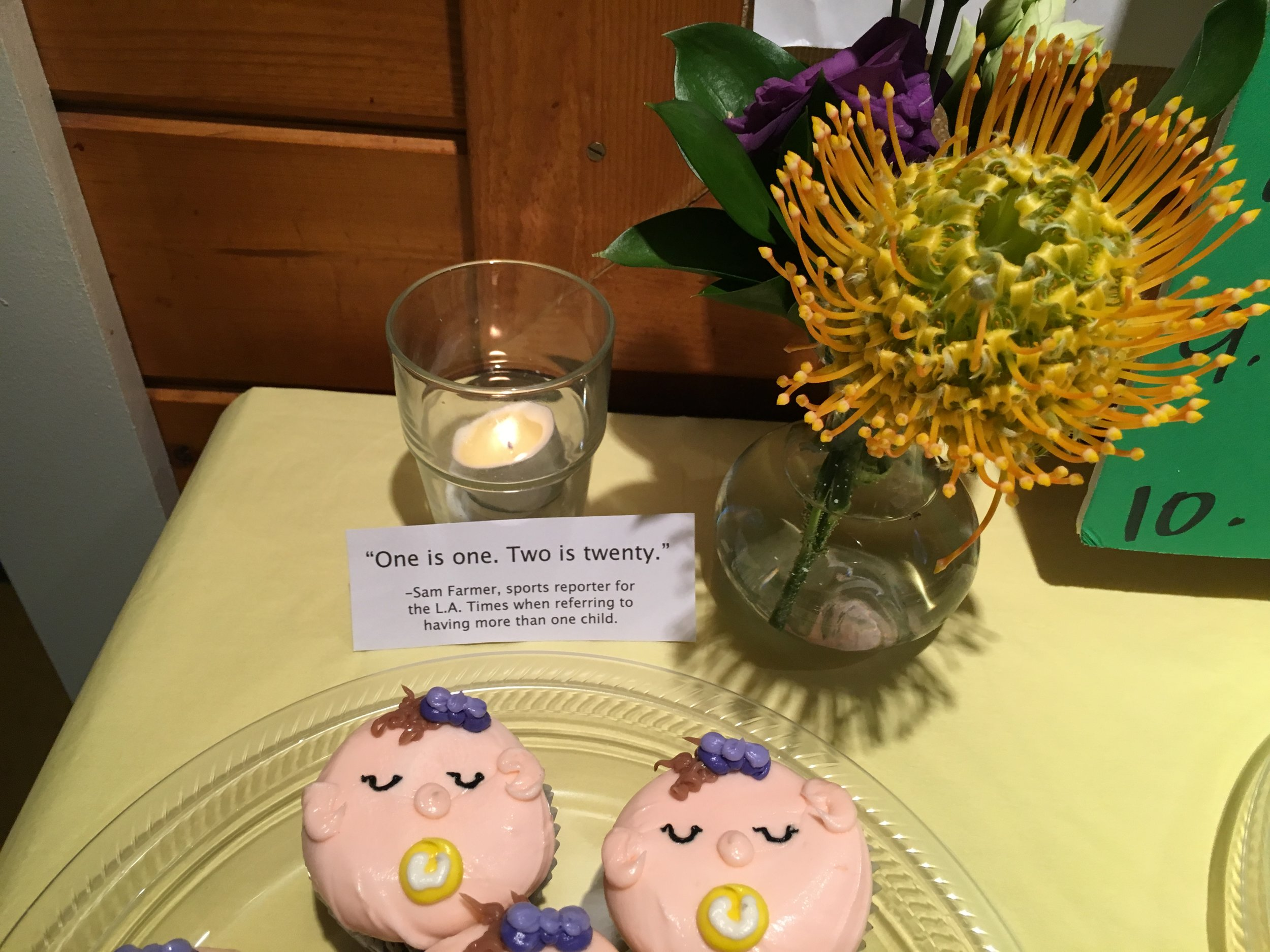 """Dessert: The boy cupcakes had yellow bow ties with purple pacifiers and the girls had purple bows in the hair with yellow pacifiers. Sam Farmer and his wife Paige came to the baby shower when I was pregnant with my second. They wrote their """"One is one. Two is twenty."""" line in my card and I have never forgotten it."""