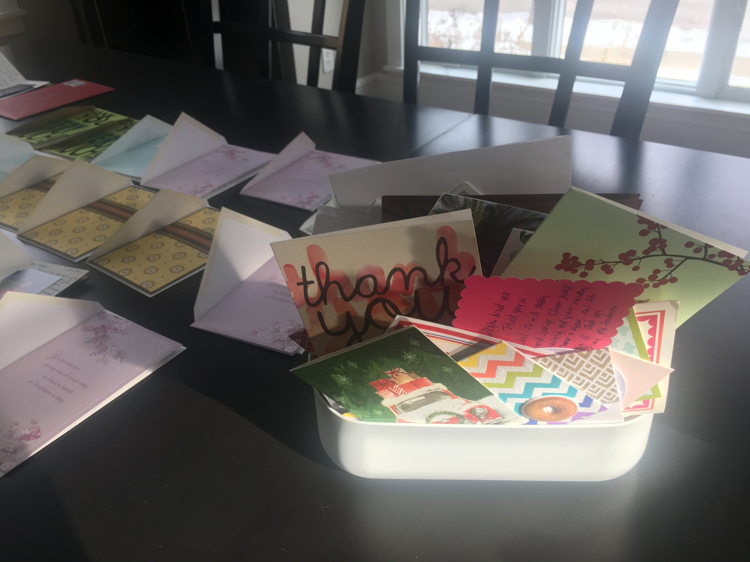 This little bin doesn't look like it but it held 107 thank you cards collected this year. Next to the bin are the cards we wrote for the kids birthdays and Christmas gifts getting ready to be signed and mailed last week.
