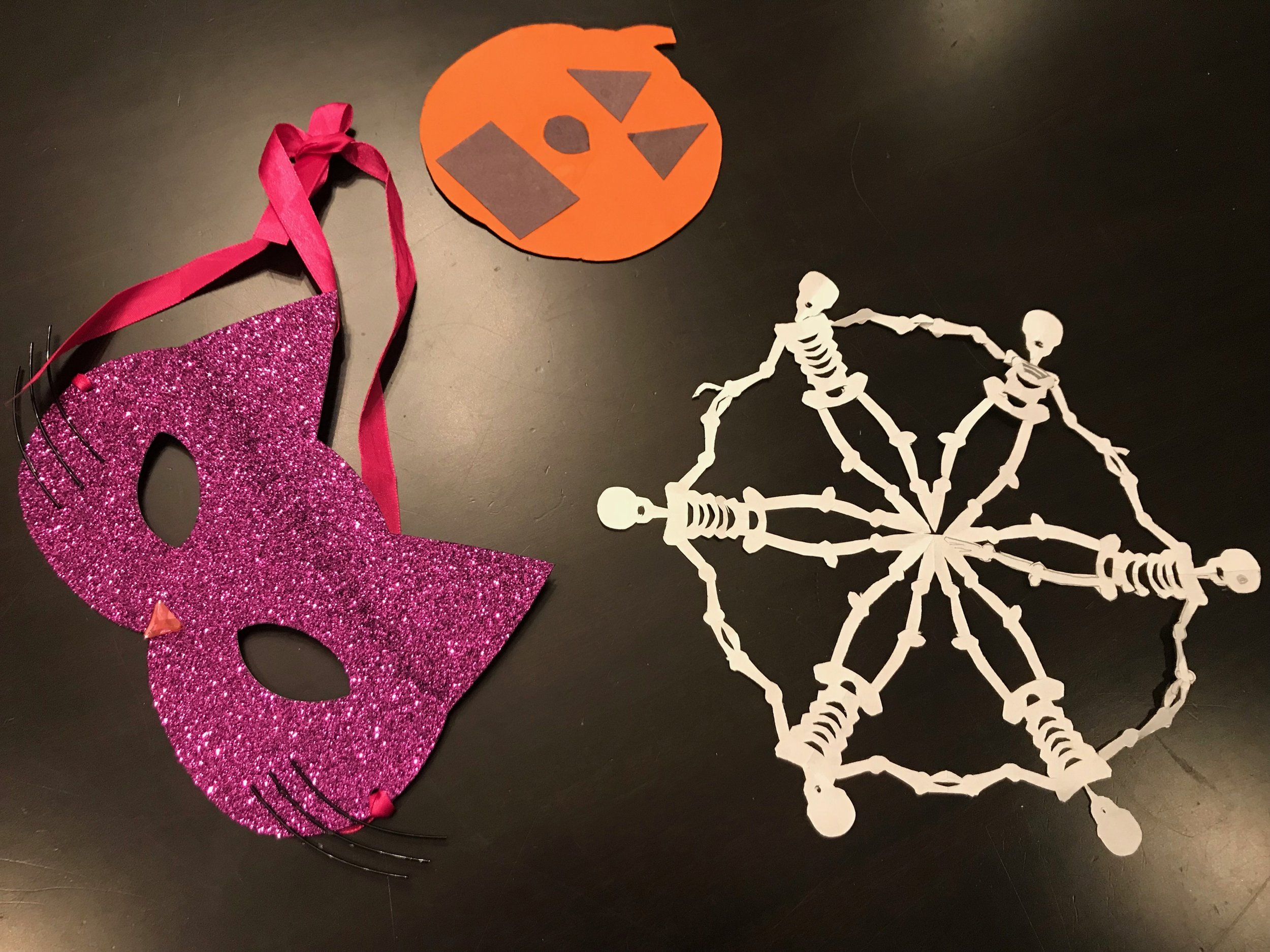 A cat mask from Auntie Camille, a jack o lantern from Jordan Martucci (who will be a doctor soon) and skeleton snowflake made by our neighbor Derek.