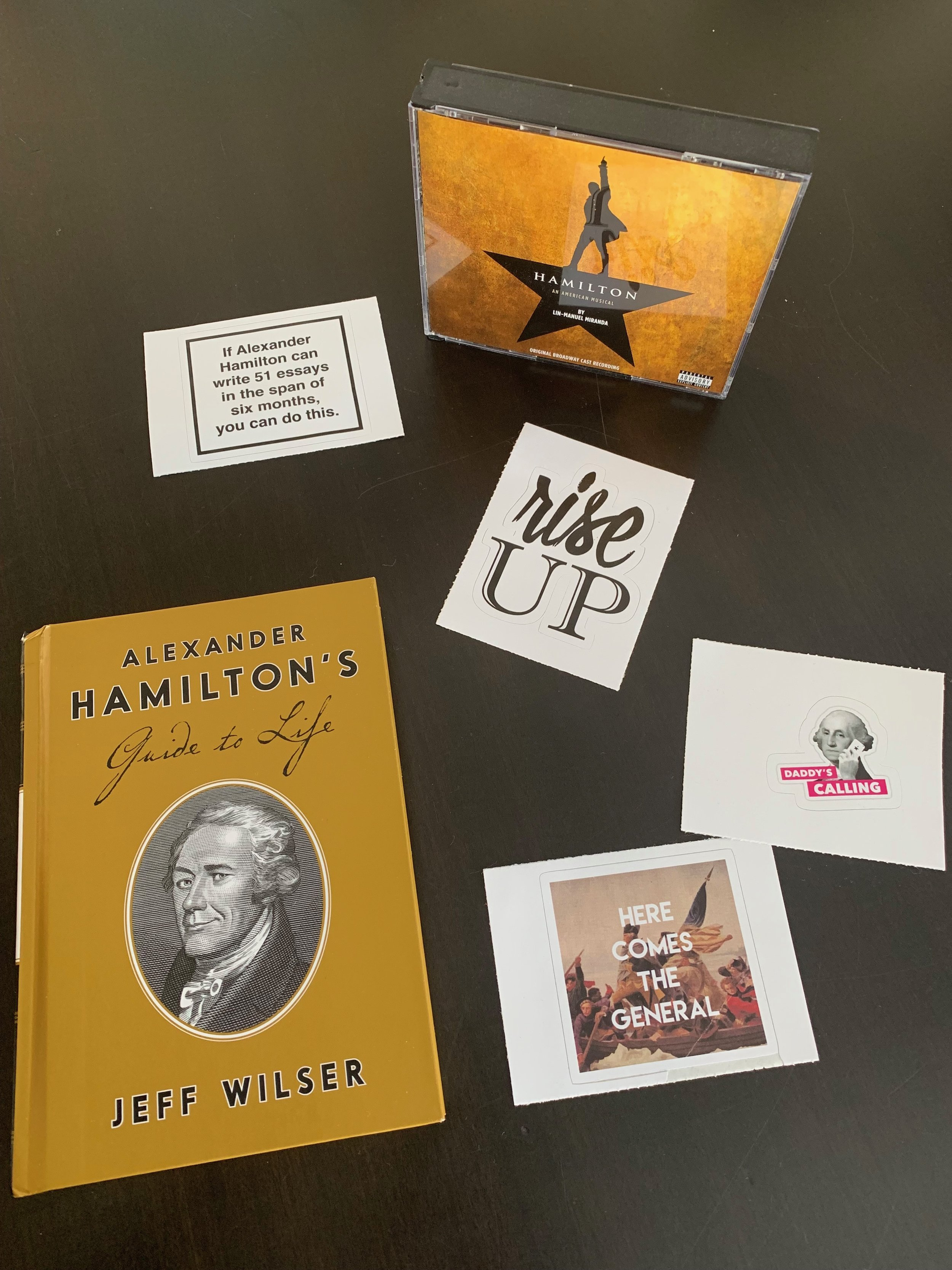 """P.S. In case you need to  pinch  a Hamilton fan in your life here are some fun items. 1)The CDs are second best to seeing the musical in person. 2)There are tons of stickers from  Red Bubble  - the one that hangs on my bulletin board is """"If Alexander Hamilton can write 51 essays in a span of six months you can do this."""" - Motivating. 3) I bought the Guide To Life book at Patina but I'm sure you know where else you can find a copy."""