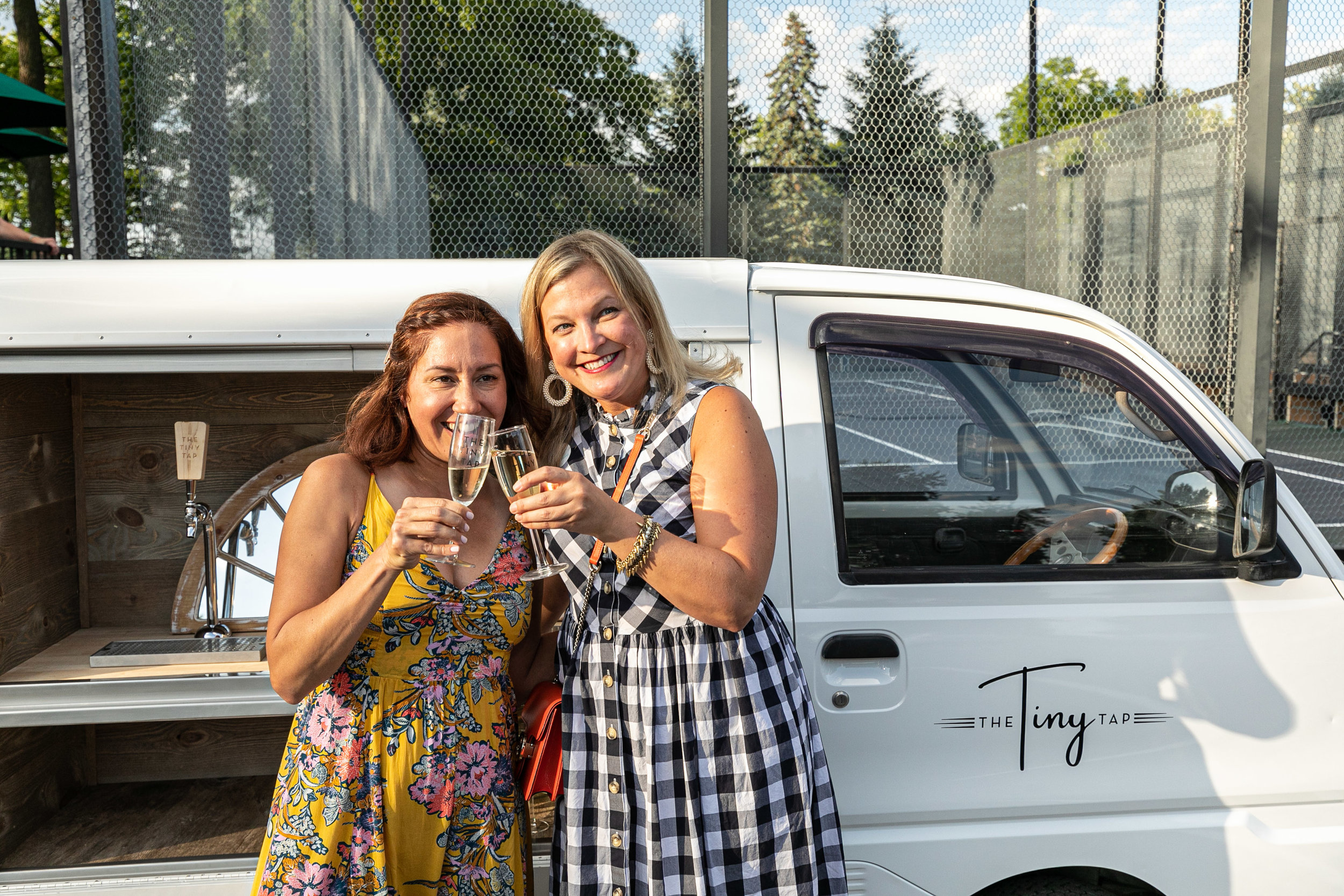 Two social media influencers - Nicole Trigger of  Live&Love MN  and Wendy Witherspoon of Stella & Dot/ VIP Style Insiders pose for a Prosecco toast at the Twin Cities Thoughtful Pinch App Launch on July 31, 2019.  Photo credit: Elliot Johnston Facebook: @propertyshotsmn, Instagram: propertyshots