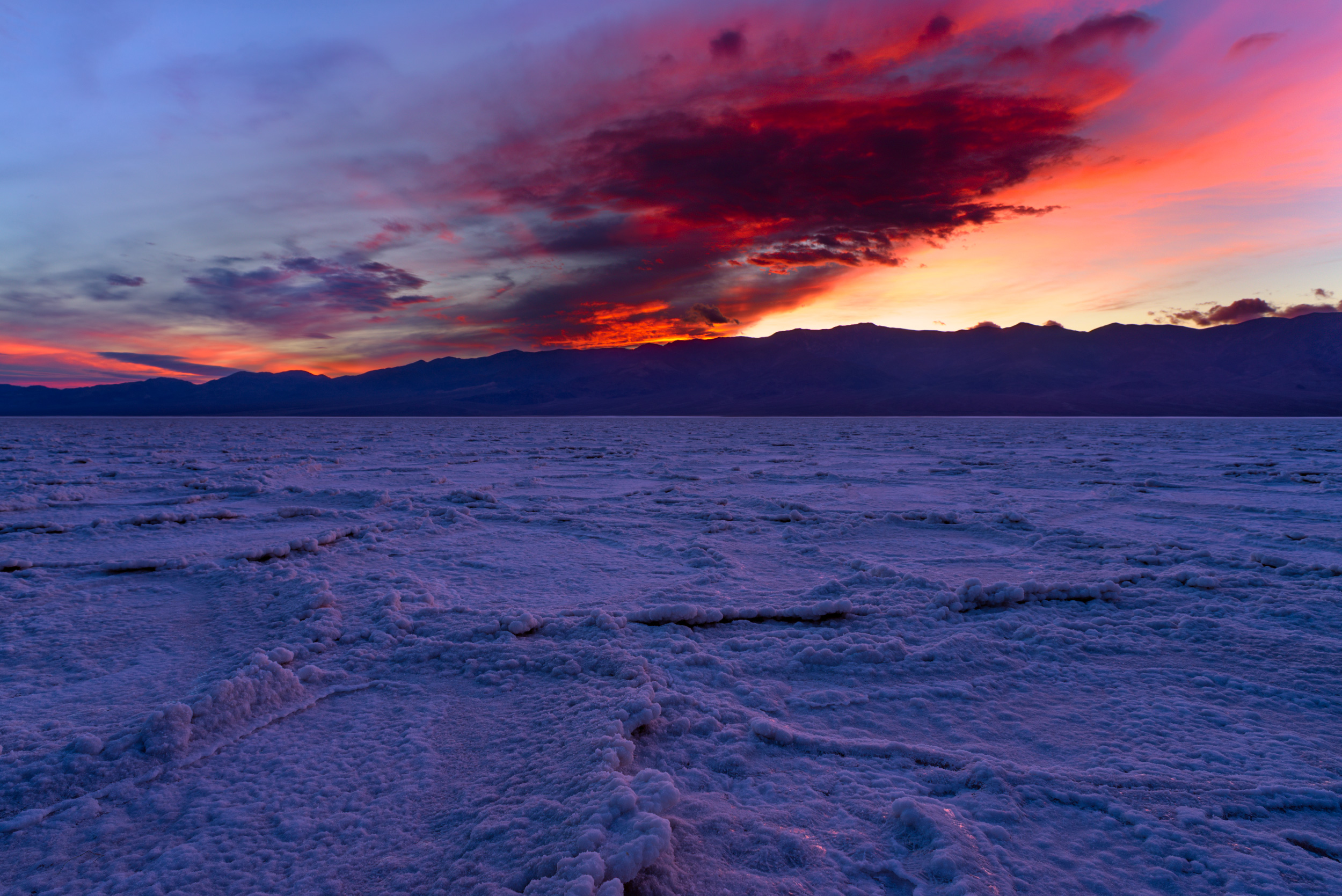 Badwater Sunset -Large thick clouds that got lit up at sunset, on the Badwater salt flats, at Death Valley.