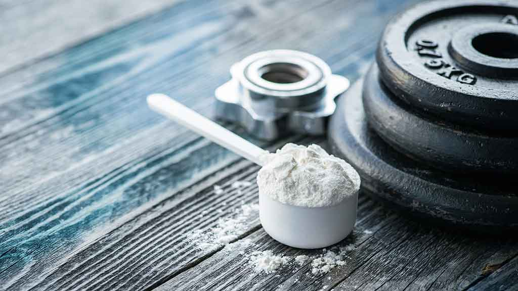 creatine in scoop with dumbell weights on table.jpg
