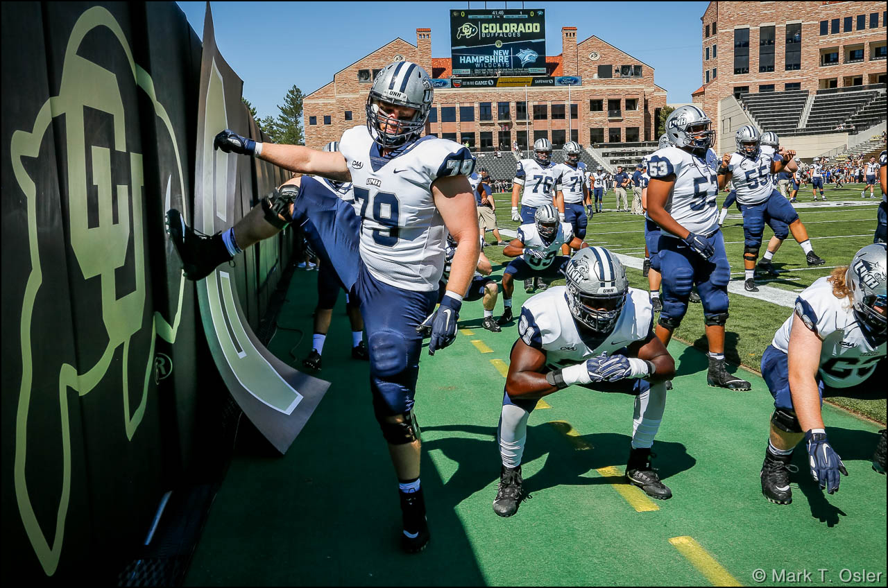 UNH offensive lineman Noah Robison (#79) uses the CU logo to limber up as he and his teammates prepare for the start of their game against the University of Colorado Saturday, Sep. 15, 2018 at Folsom Field in Boulder.
