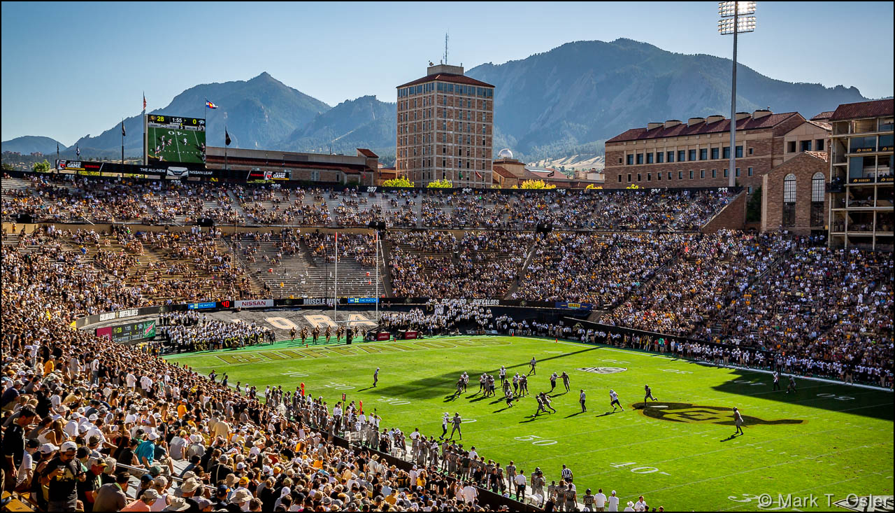 The UNH offense battles against the CU defense on the New Hampshire side of the field in the first half of UNH's game against CU in scenic Boulder, CO, at the base the Rocky Mountains. Temperatures were in the 90s at game time.