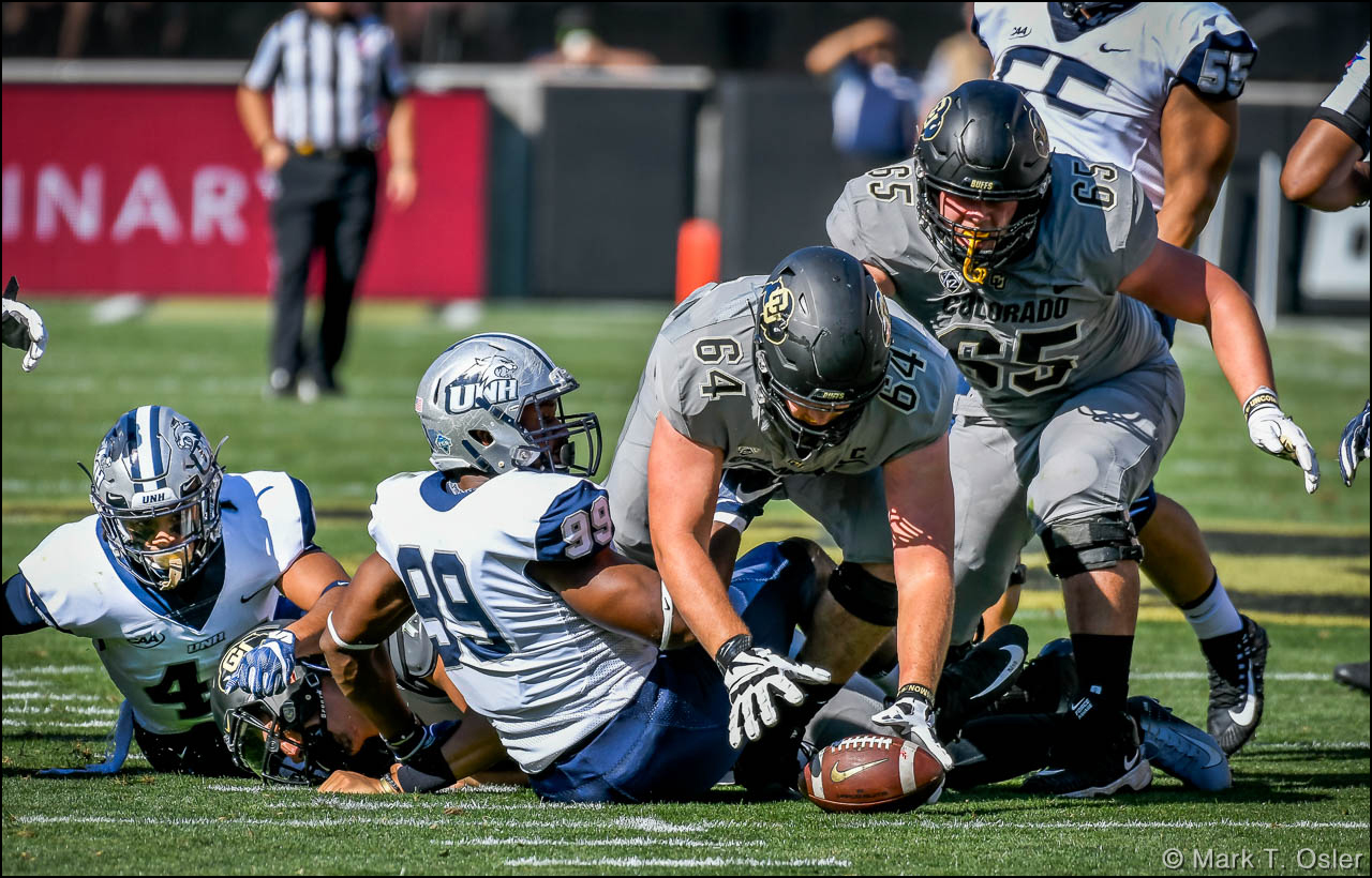 CU safety Pop Lacey (#40, far left) knocked the ball loose from quarterback Steven Montez (#12, face down) while Montez was being tackled by UNH defensive end Brian Carter (#99) in the second quarter. CU offensive tackle Aaron Haigler (#64) recovered the fumble. Also in pursuit for CU is center Colby Pursell (#65).