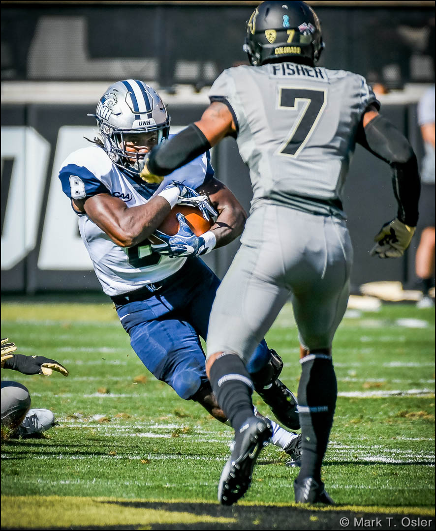 UNH running back Trevon Bryant (#8) evades CU safety Nick Fisher (#7) for a 4-yard gain in the first quarter.