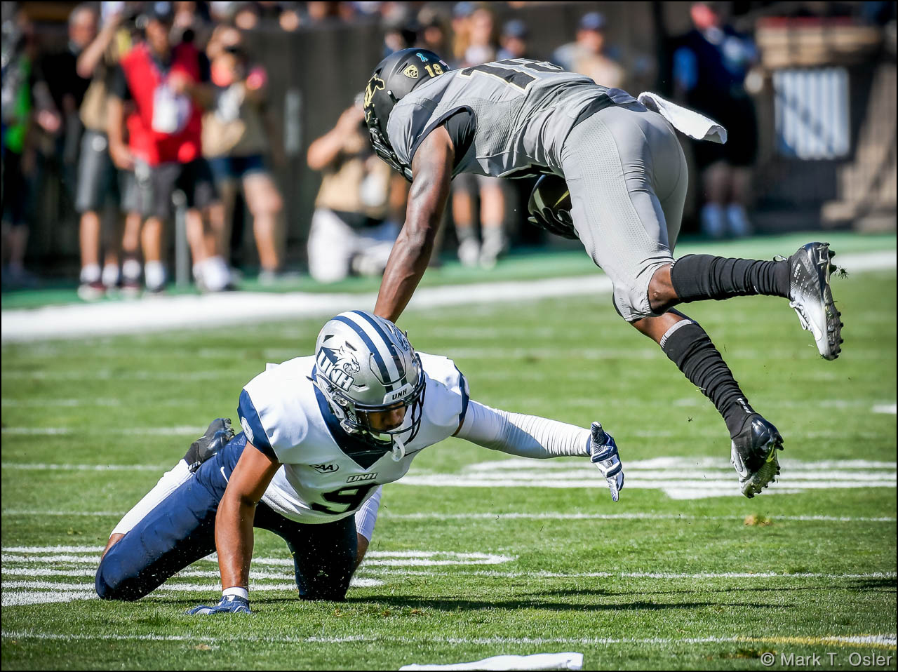 UNH cornerback Isiah Perkins (#9) takes down CU wide receiver Tony Brown (#18) for a 2-yard gain during the first quarter.