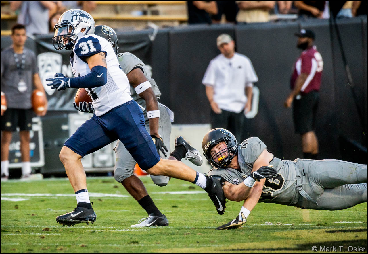 CU defensive back Chase Newman (#46) makes an unsuccessful attempt to stop UNH wide receiver Nick Lubischer (#31) on a 37-yard pass play to CU's 32 yard line with 1:05 remaining in the game. The Wildcats only made it to CU's 22 yard line before time ran out.