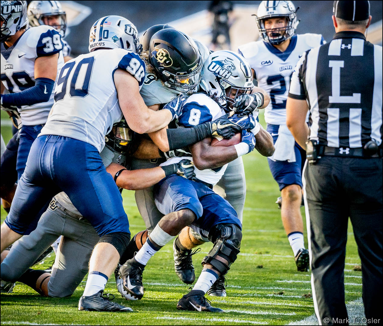 UNH's Carson Leary (#90) tries to move the pile forward as kickoff returner Trevon Bryant (#8) is wrapped up by CU's Aaron Maddox (#9) and Javier Edwards (#33, underneath) on a kickoff return following a CU field goal near in the third quarter.