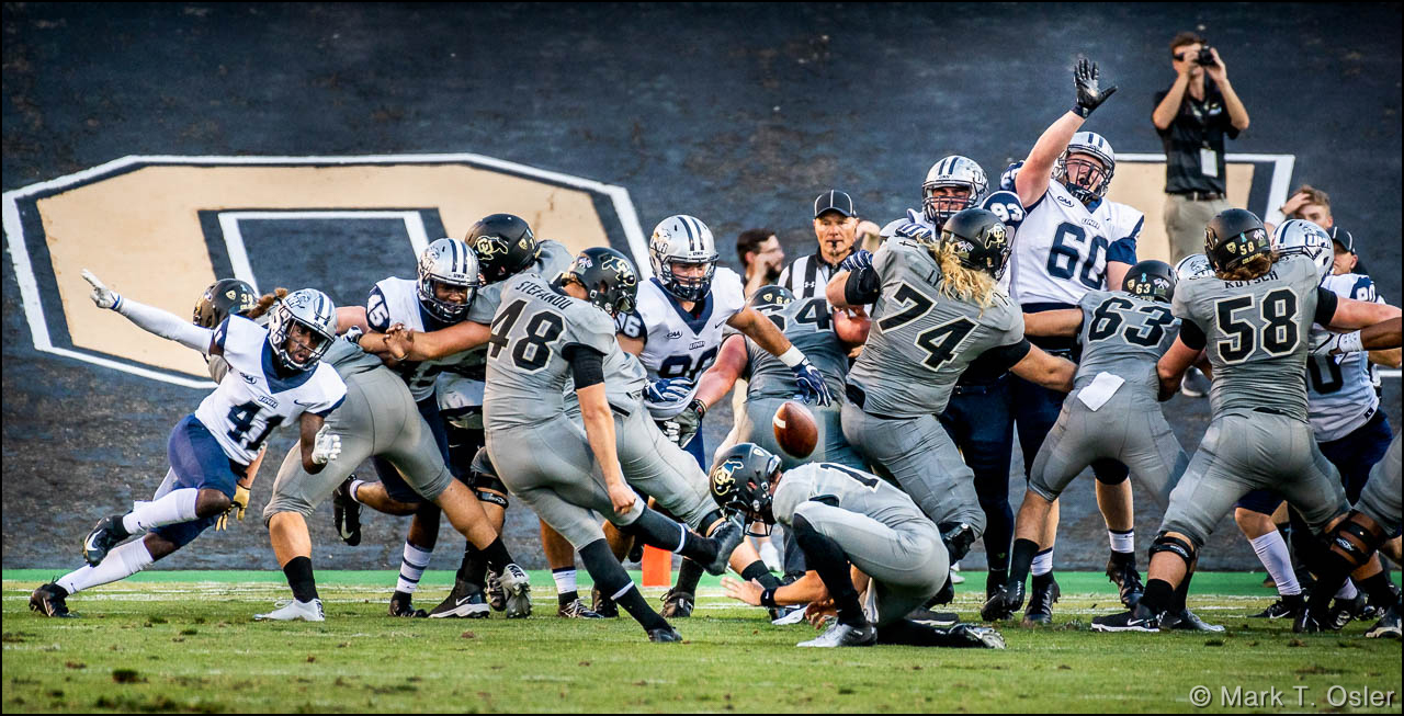 UNH defends against a CU extra point attempt by kicker James Stefanou (#48). Stefanou's successful conversion was the final point of the game, putting CU ahead 45-14.