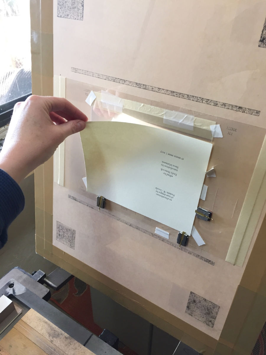 "The first step is to place, or ""hang,"" the sheet of paper-to-be-printed on the tympan. You can see the little metal guides that keep the page in the correct spot. (You can also see the words in black ink that I printed earlier in the week.)"